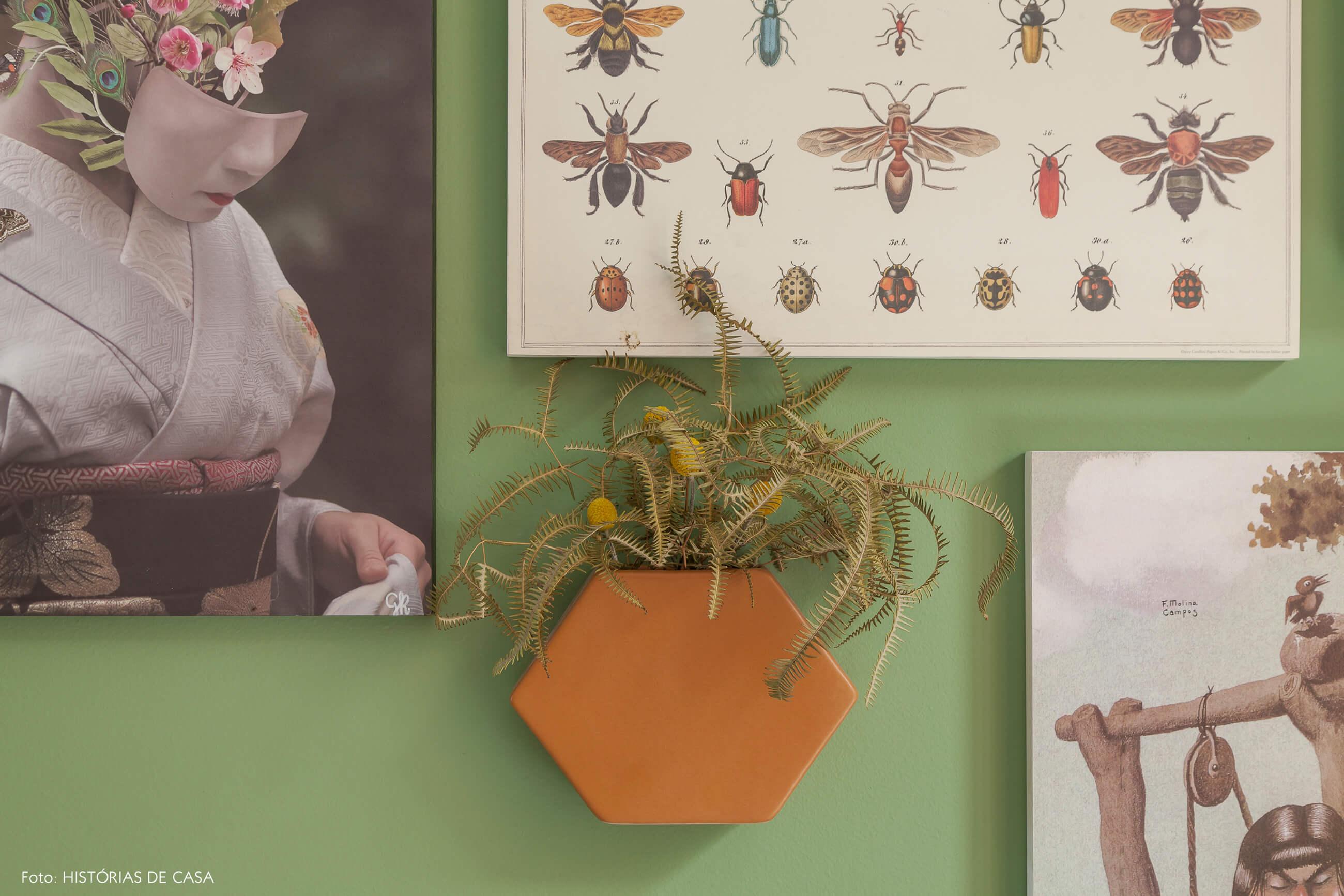 Sala com parede pintada de verde e vaso suspenso