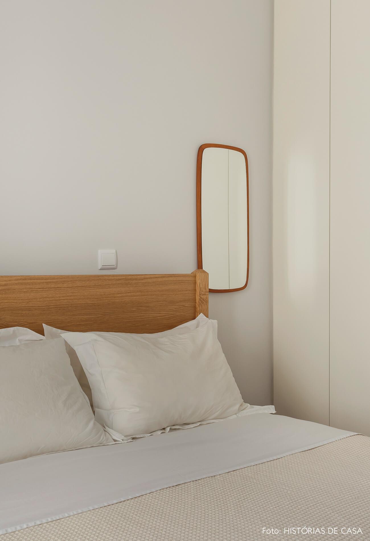 Quarto com cama de madeira e tons neutros