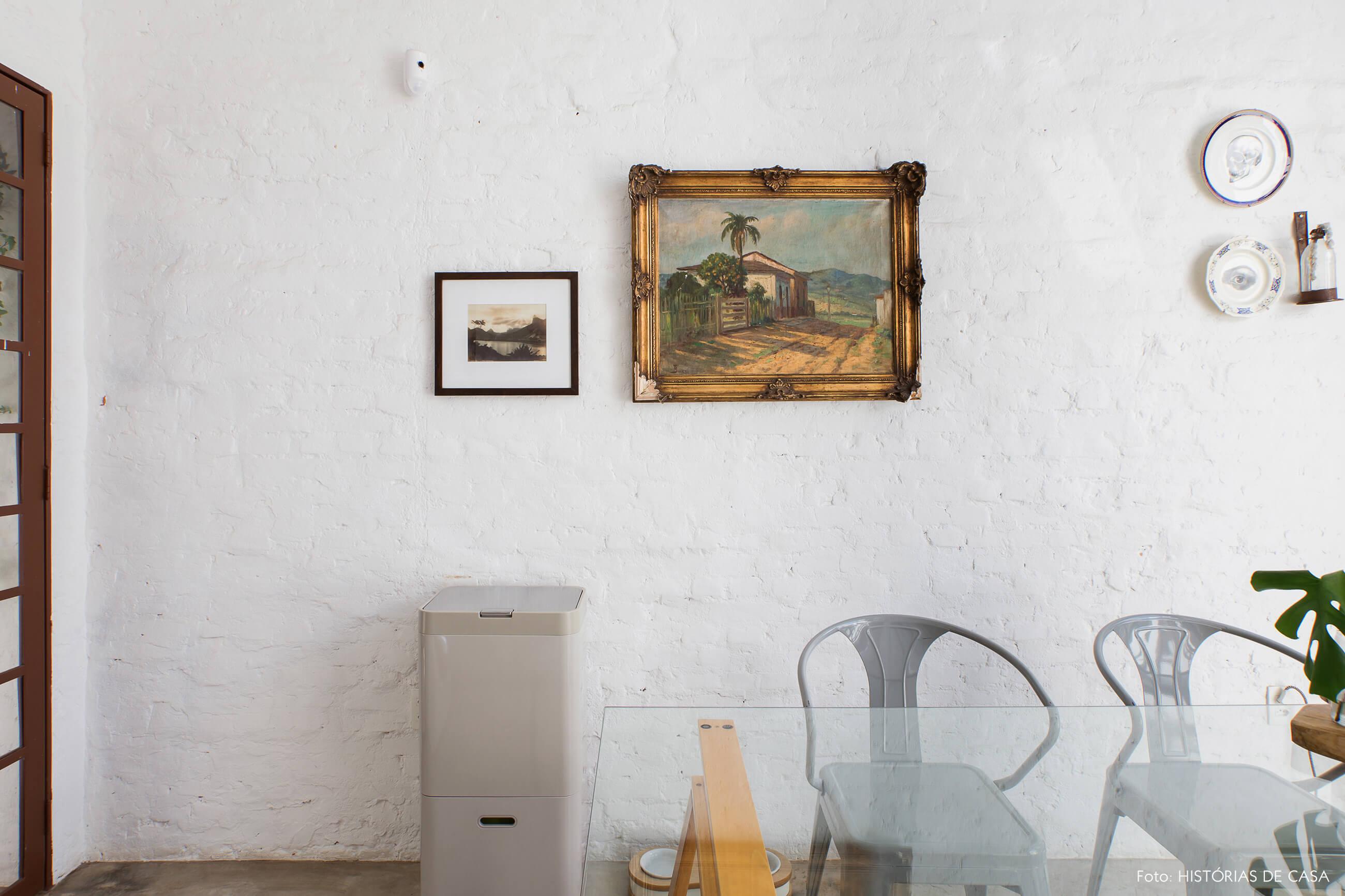 Cozinha com parede de tijolinhos brancos e quadros