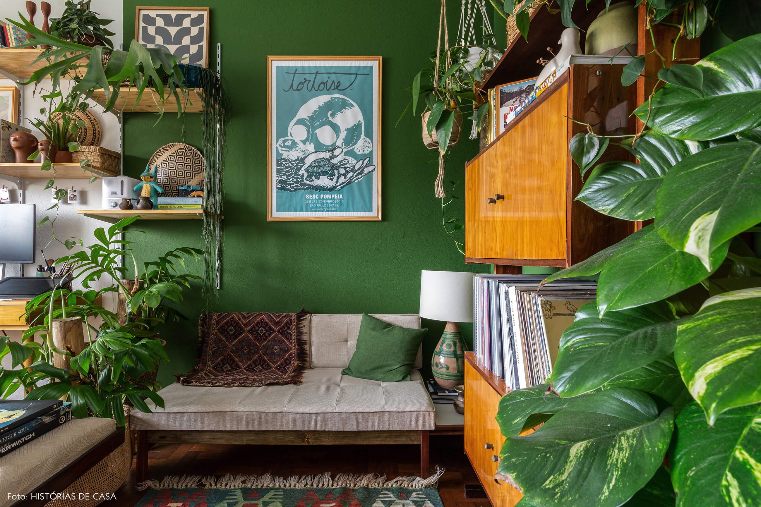 Home office com paredes pintadas de verde e móveis vintage