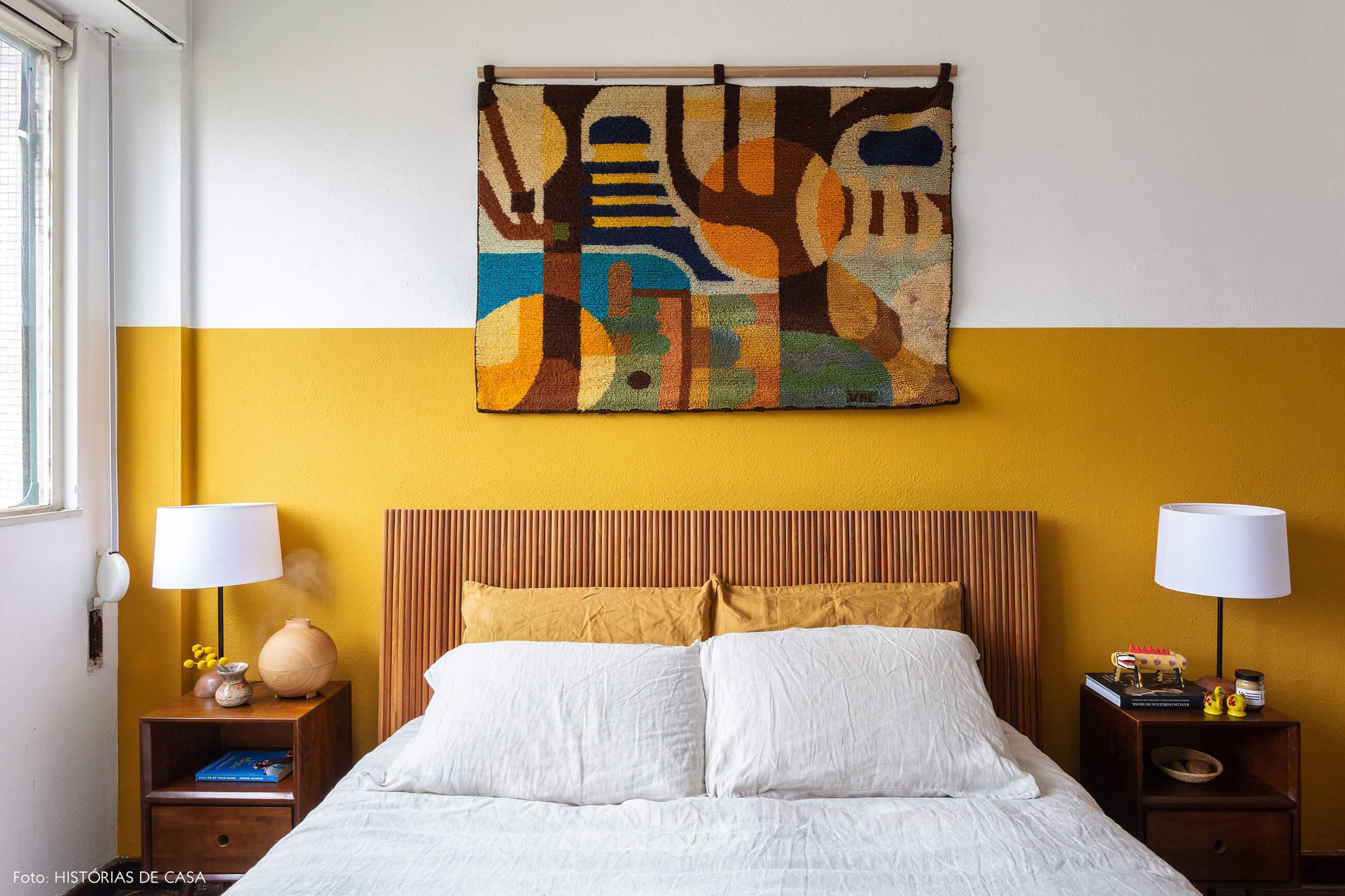 Quarto com cama de madeira e parede mostarda