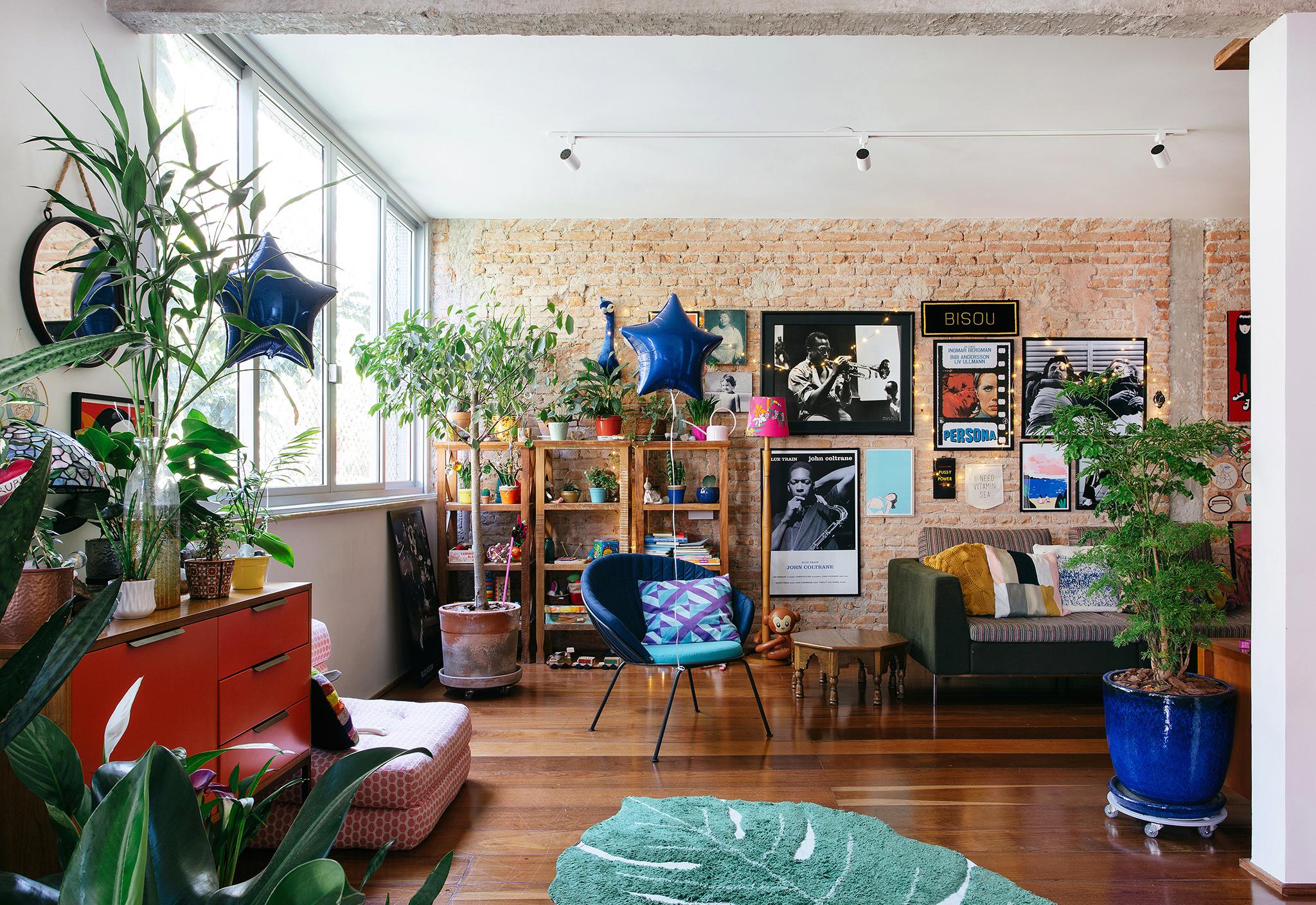Sala com parede de tijolinho e muitos quadros