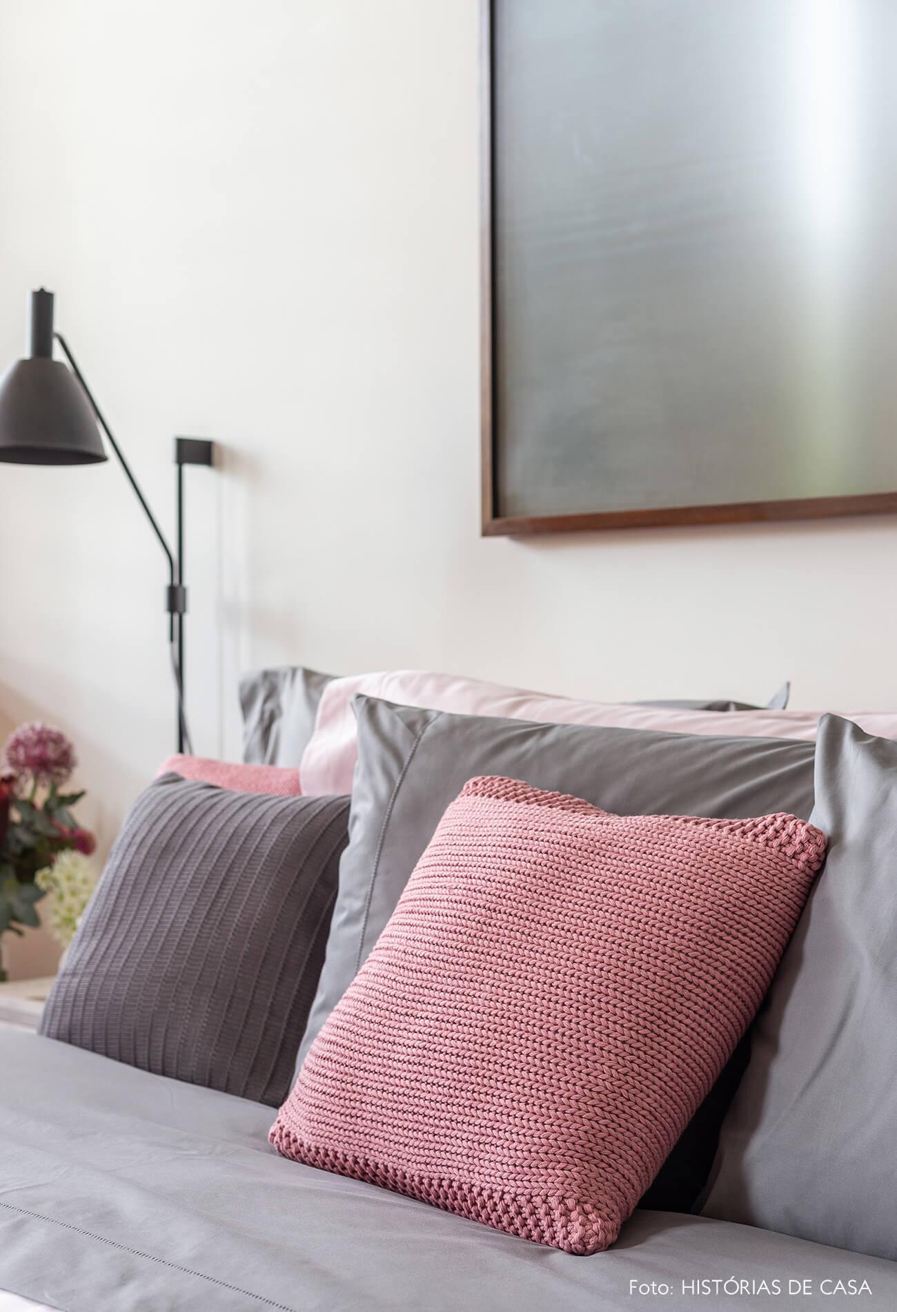 Quarto de casal com roupa de cama cinza e rosa, almofada de tricô