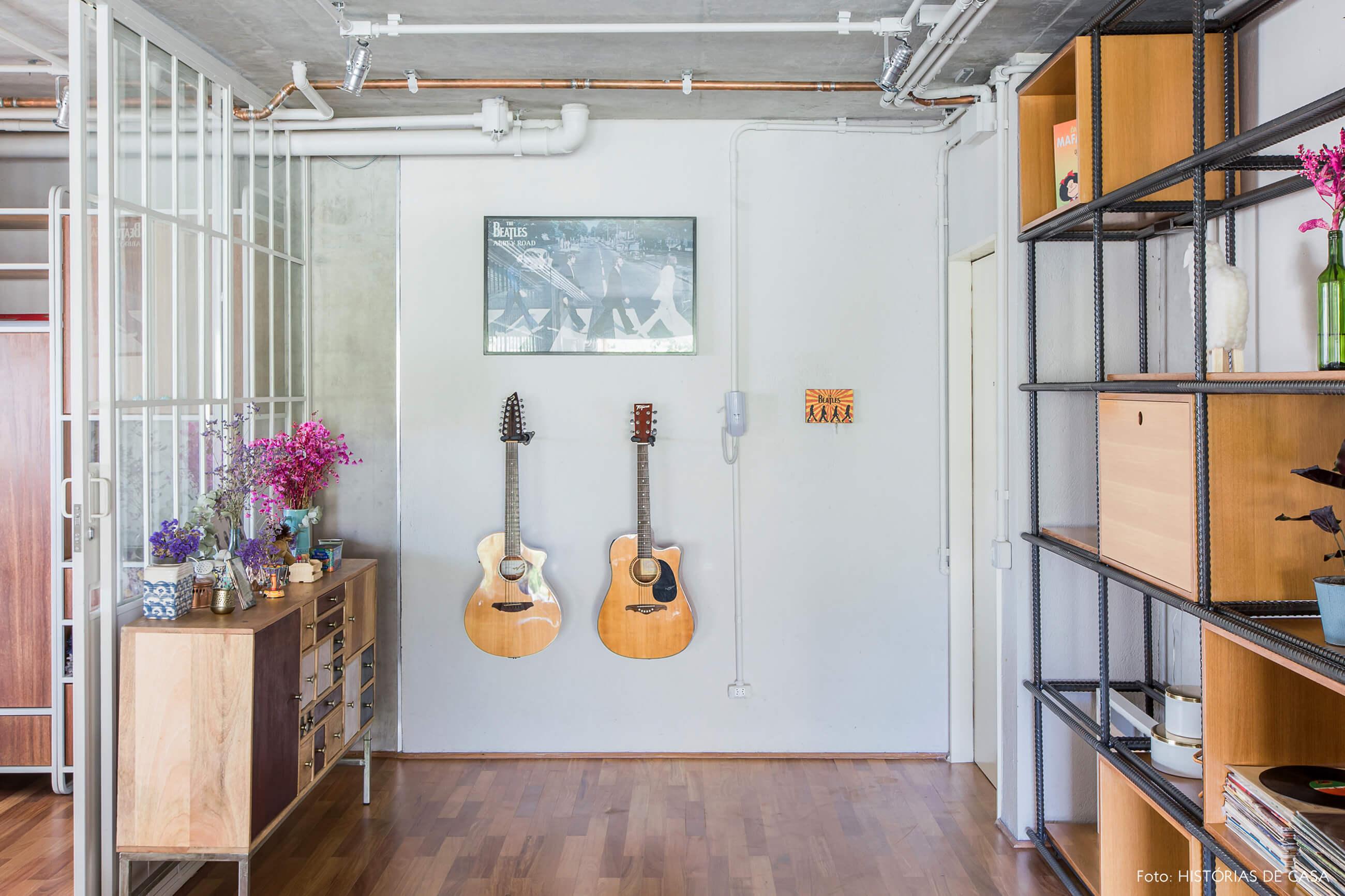 Hall de entrada com violão e tubulação aparente