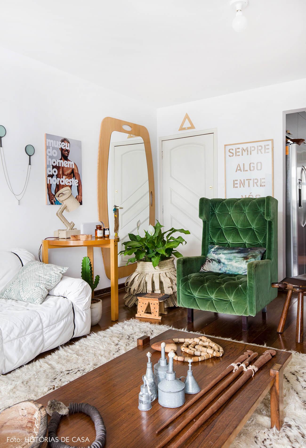 Sala com tons neutros e poltrona verde