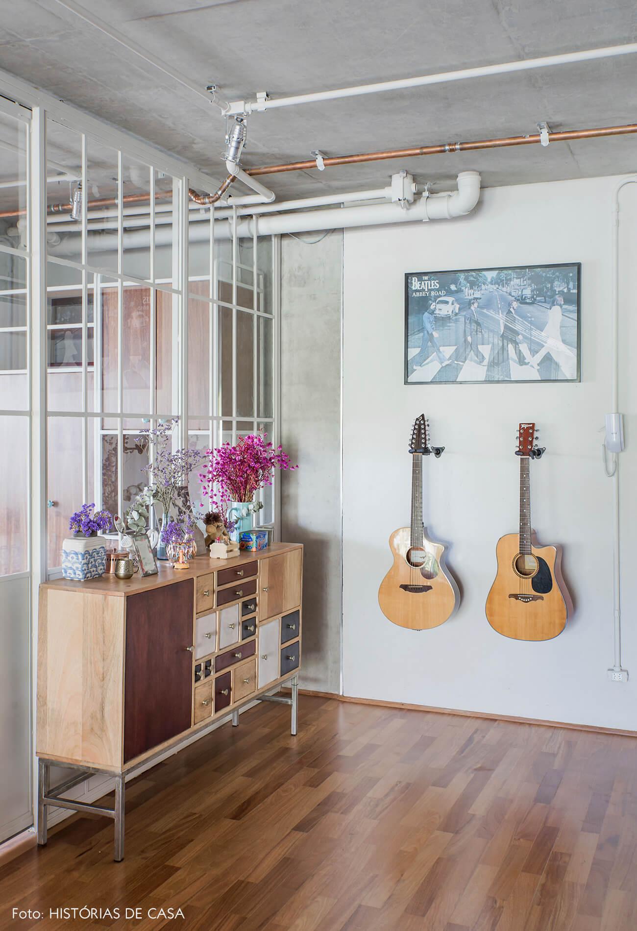 Hall de entrada com portas de serralheria e violão na parede