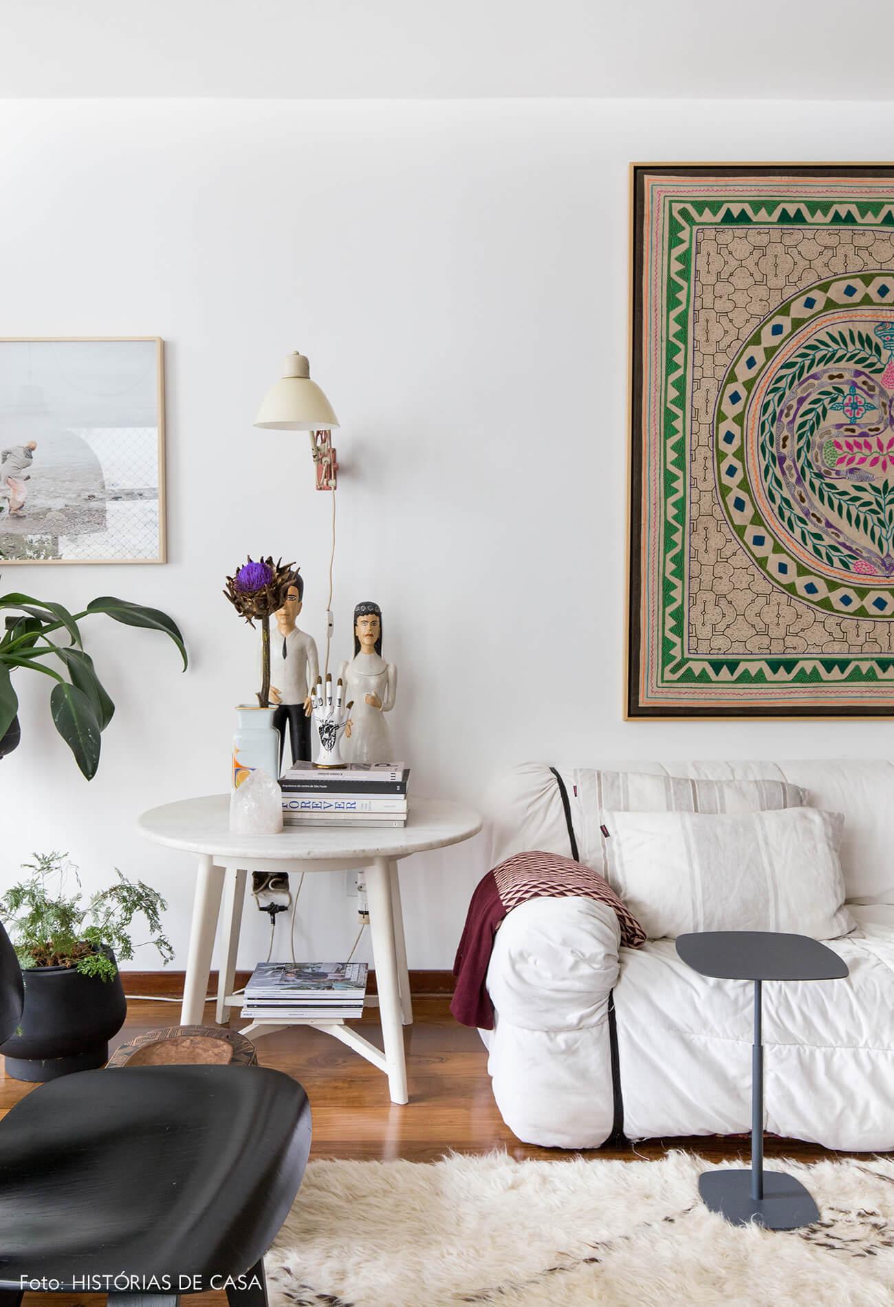 Sofá branco Strips, mesa lateral branca e objetos de arte popular