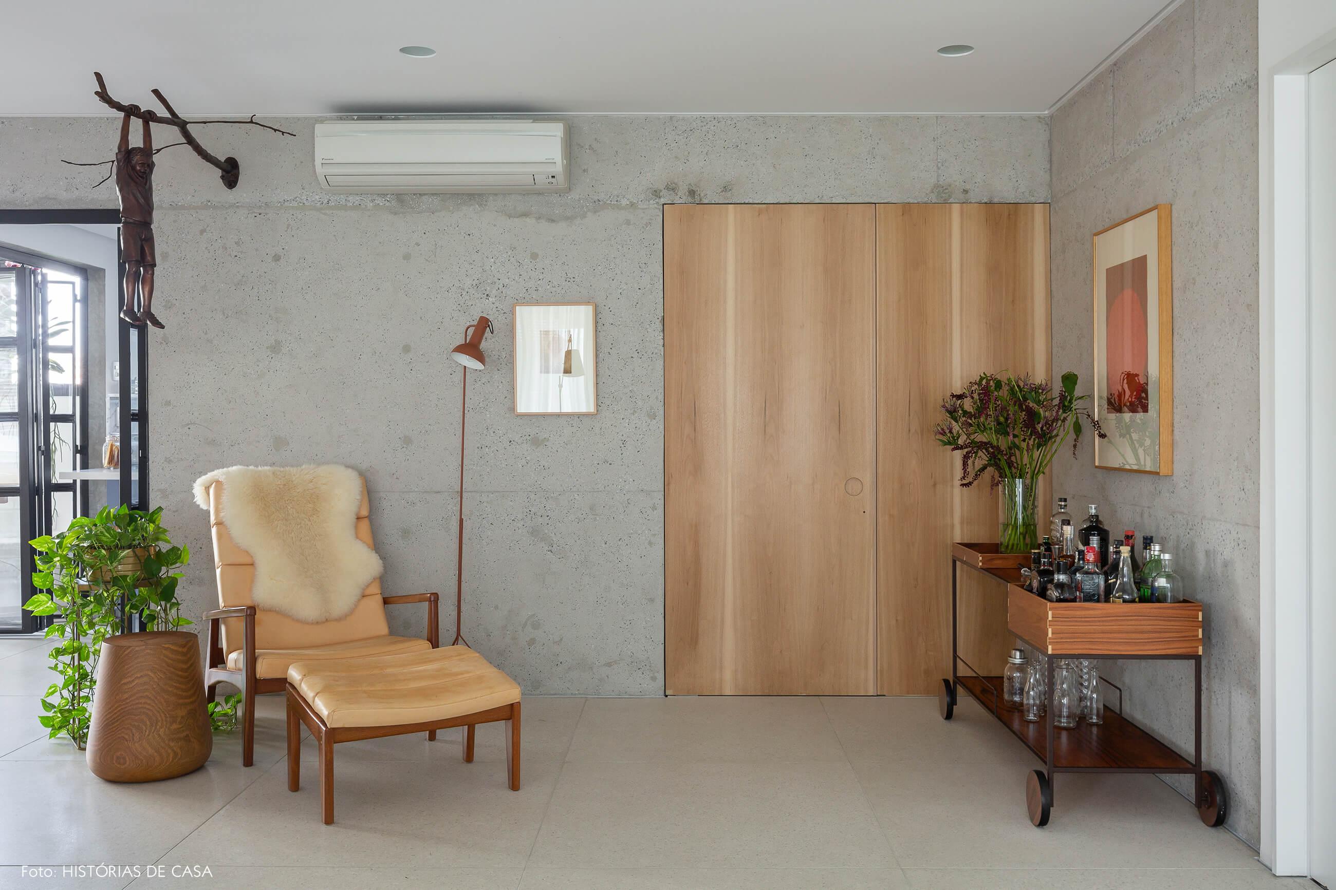 Sala com parede de concreto e painel de madeira