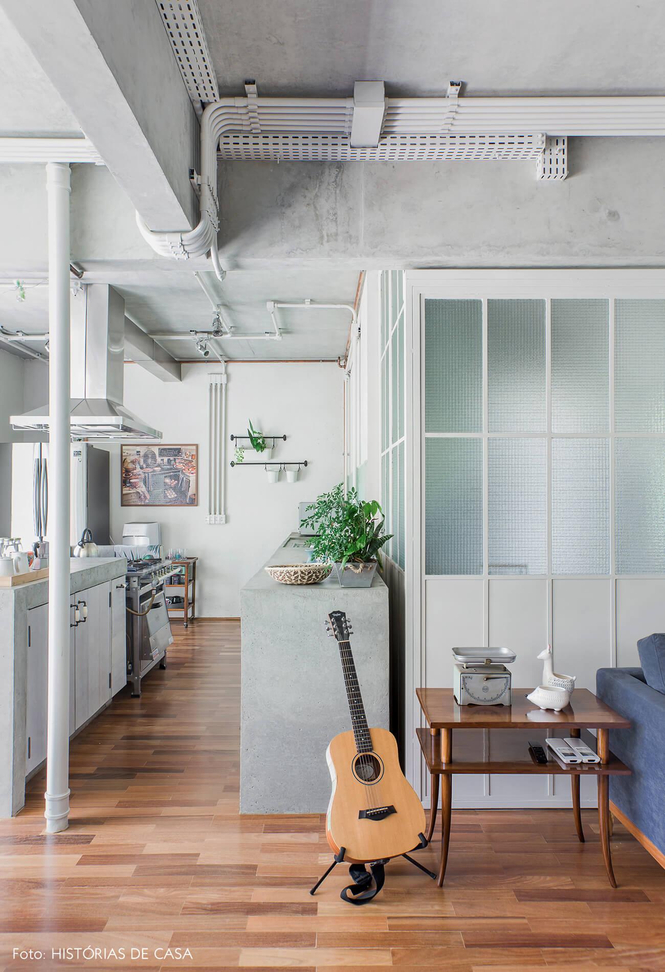 Apartamento com sala integrada e cozinha com bancada de concreto