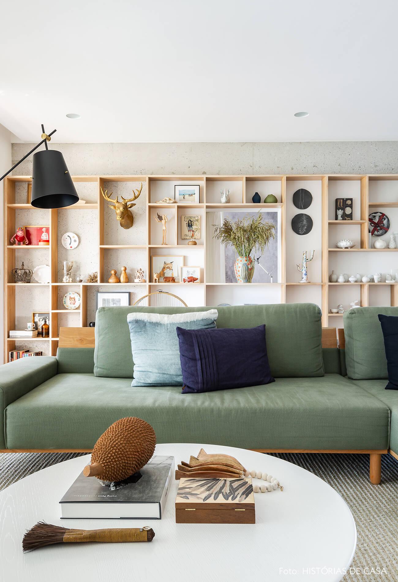 Sala com sofá verde e estante de madeira clara