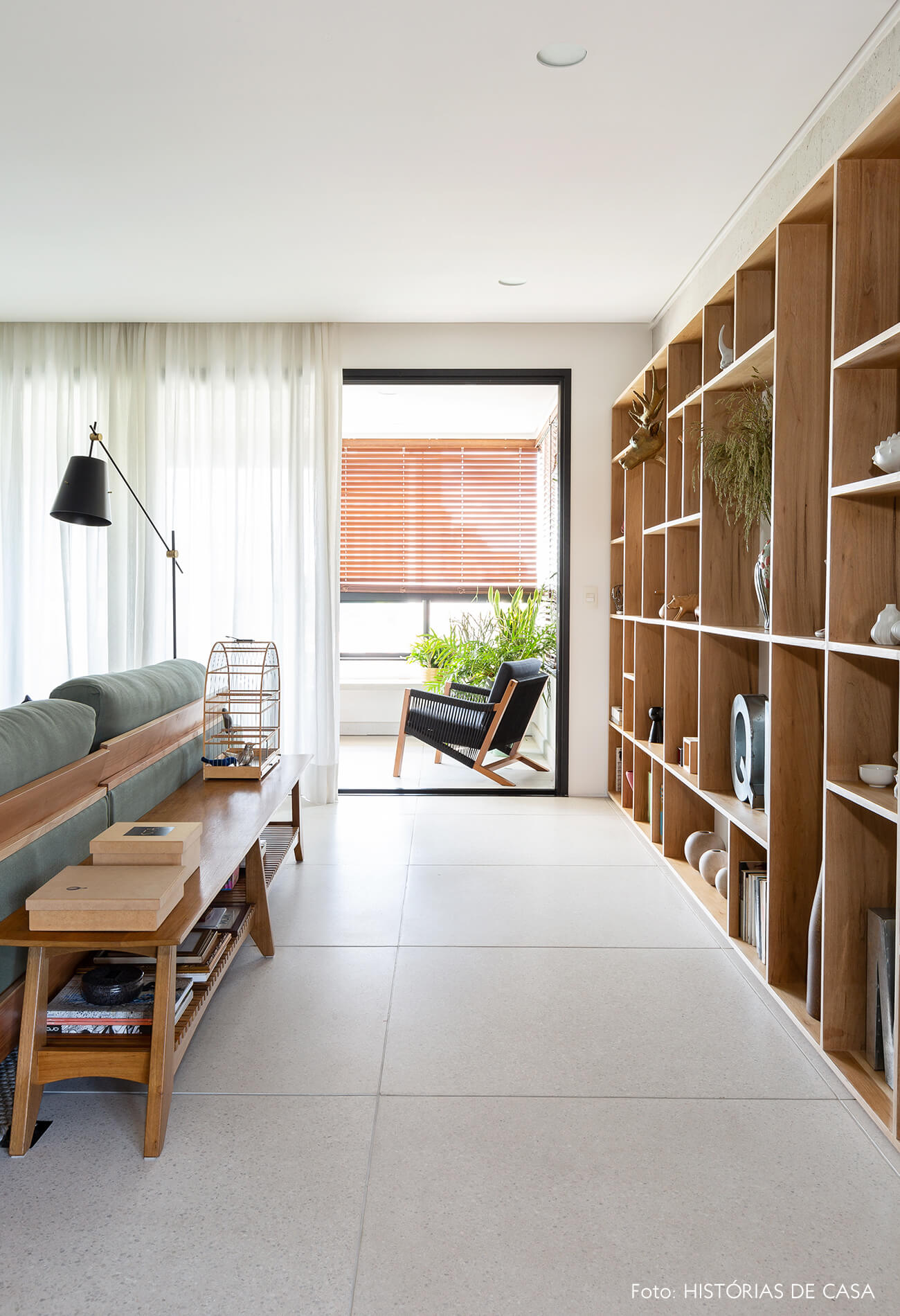 Sala com banco atrás do sofá e estantes de madeira
