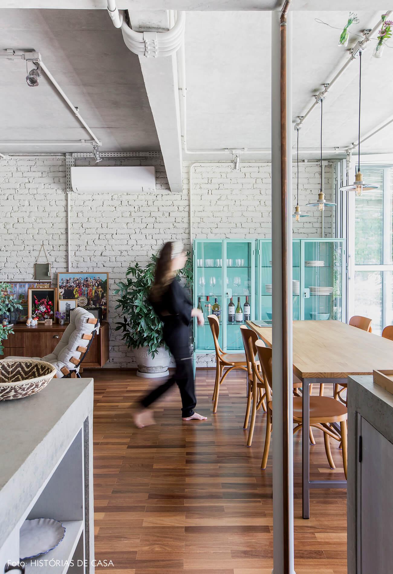 Sala de jantar integrada com paredes de tijolinho e cristaleira colorida
