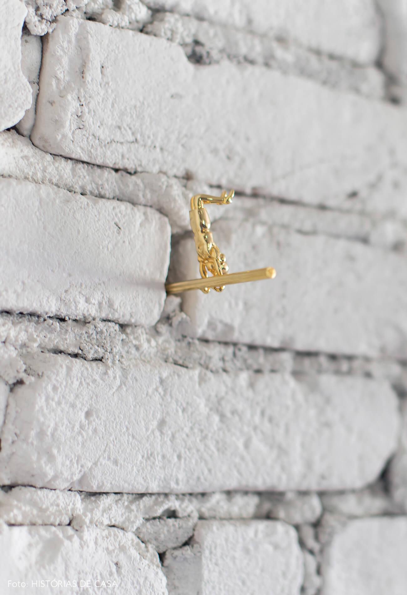 Sala de jantar integrada com paredes de tijolinho e escultura dourada
