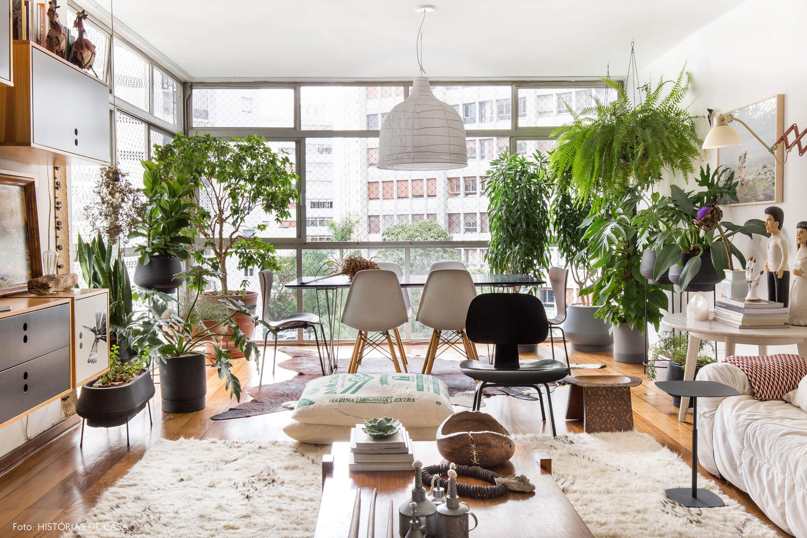 Sala de jantar com plantas, grandes janelas e tons neutros
