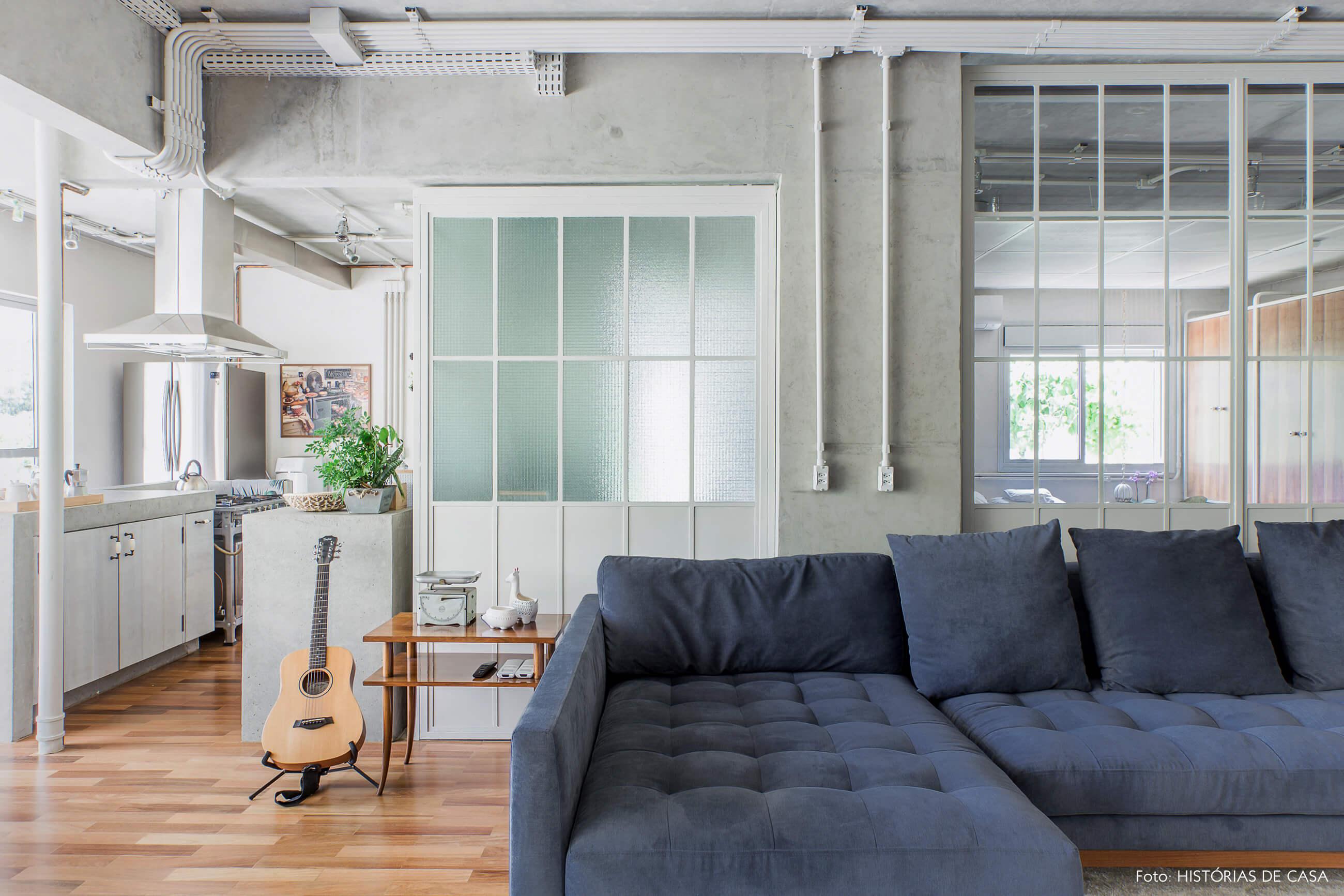 Sala integrada com paredes de concreto e serralheria