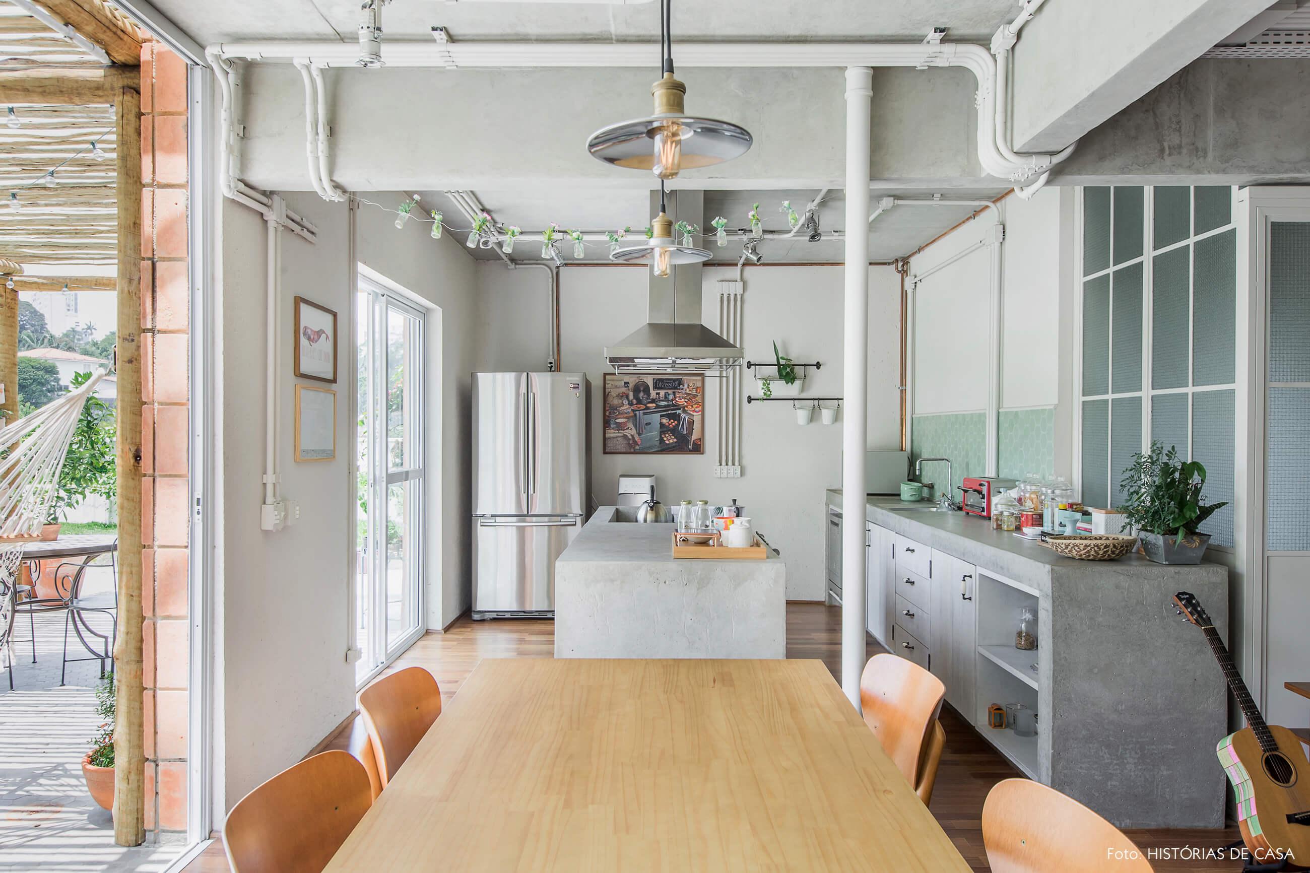 Sala de jantar integrada com a cozinha, com estruturas de concreto aparente