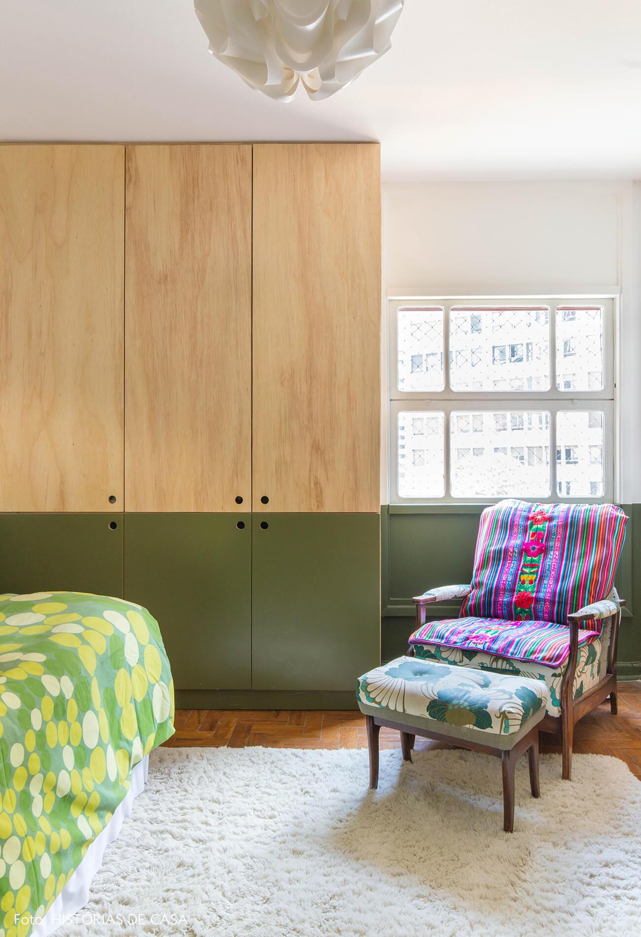 Quarto de hóspedes com meia parede pintada de verde e armário