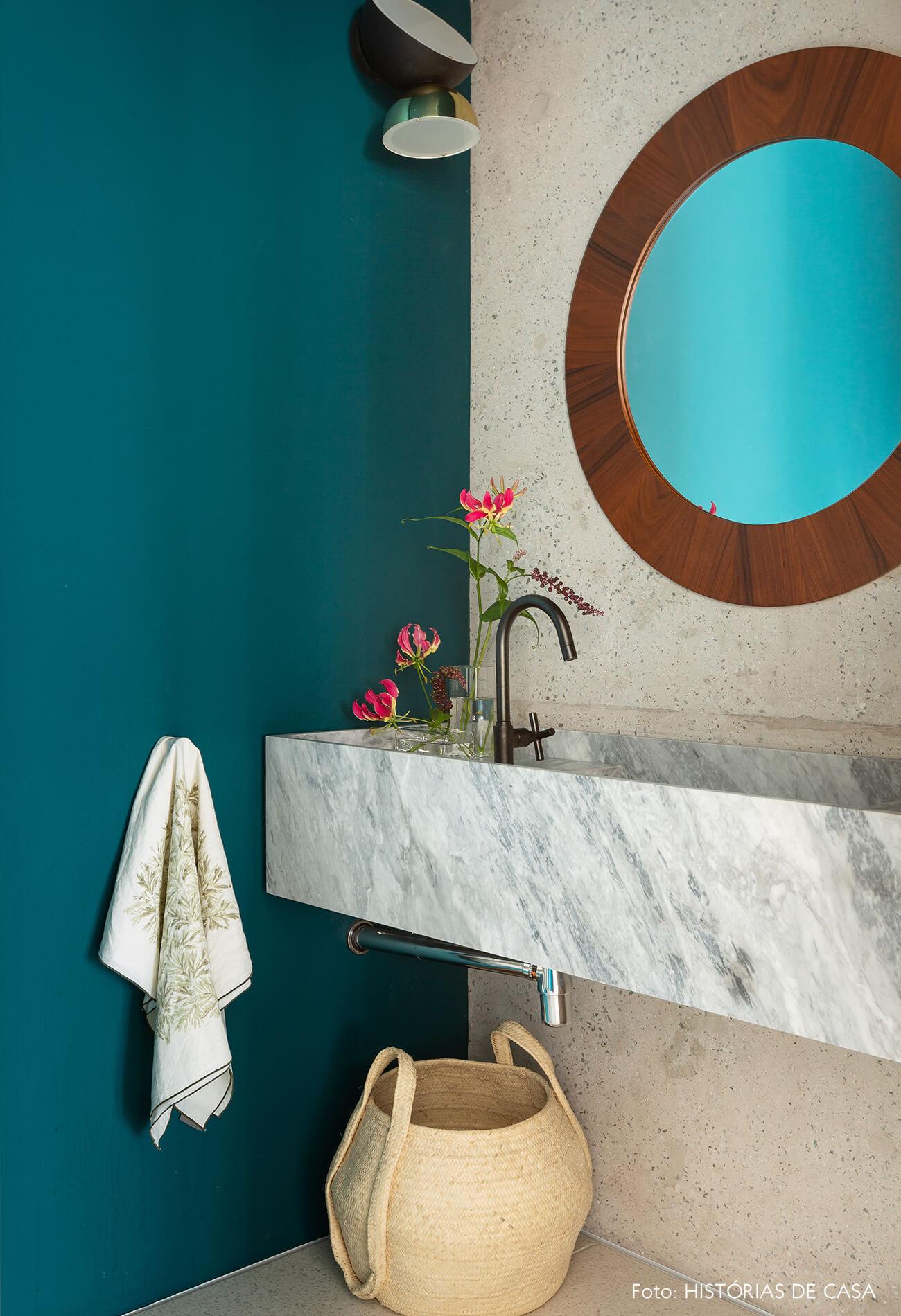 Lavabo com parede colorida e espelho redondo