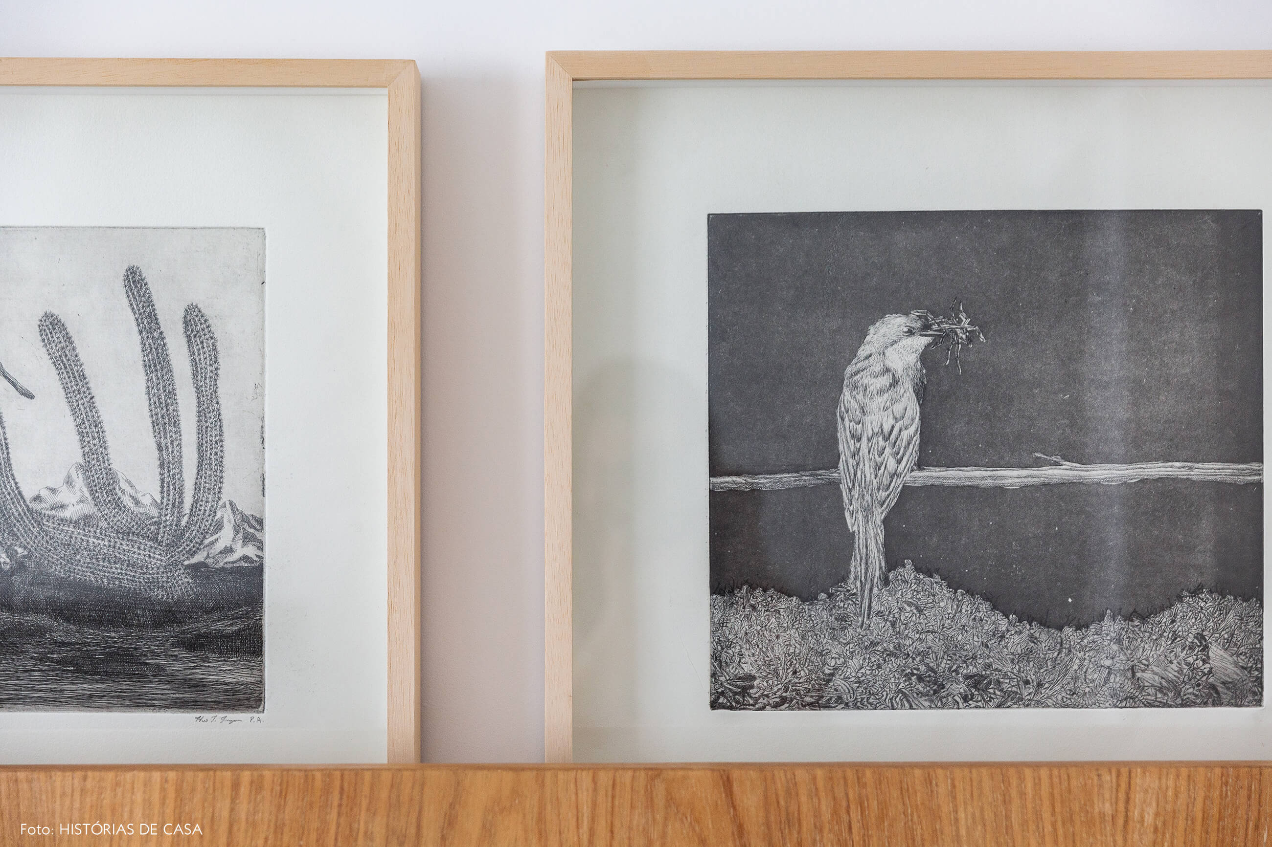 Quarto com cabeceira de madeira e gravuras em preto e branco