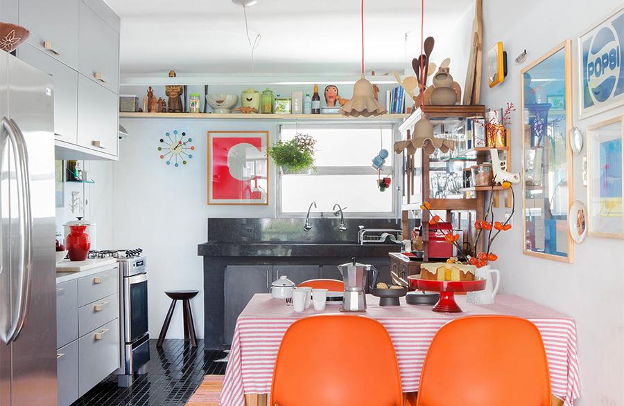 Cozinha com cadeiras coloridas e piso preto