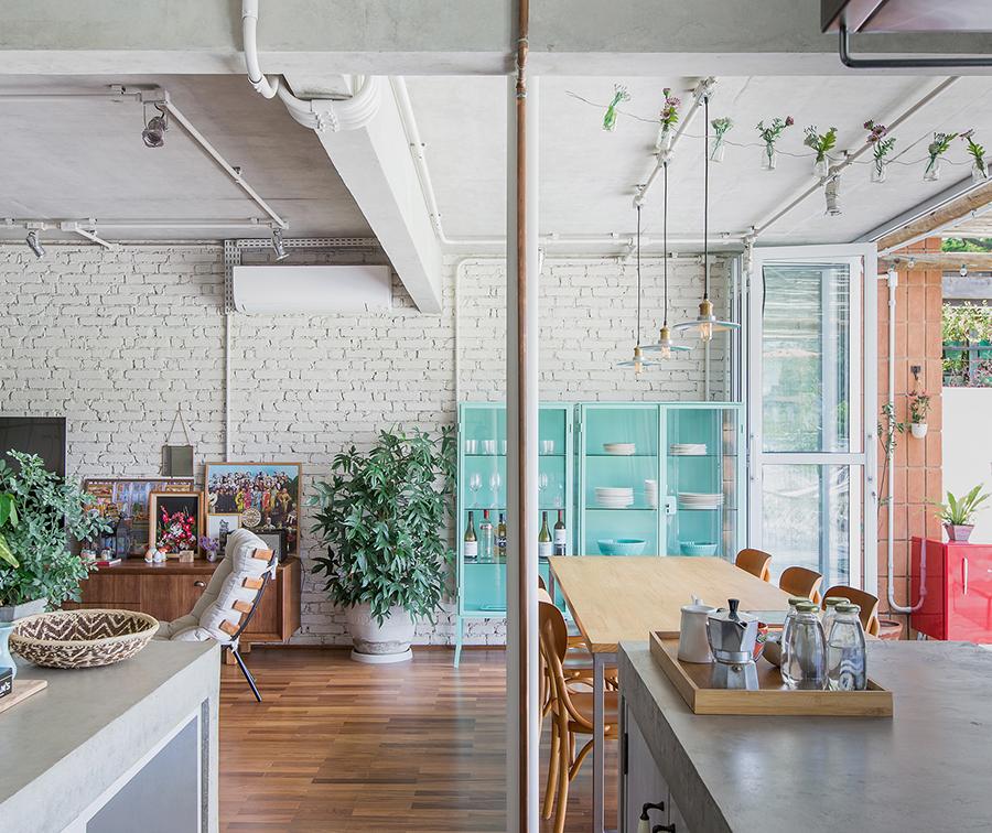 Sala de jantar com parede de tijolinho e cristaleira colorida