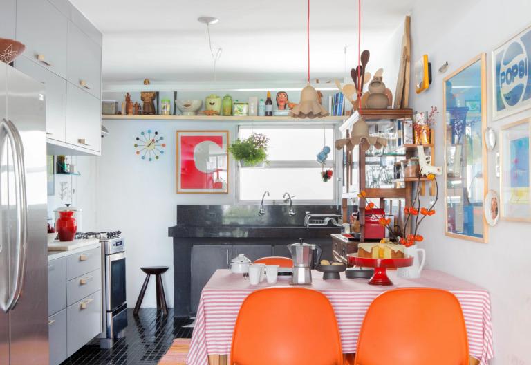 Cozinha com cadeiras laranja e acabamentos pretos