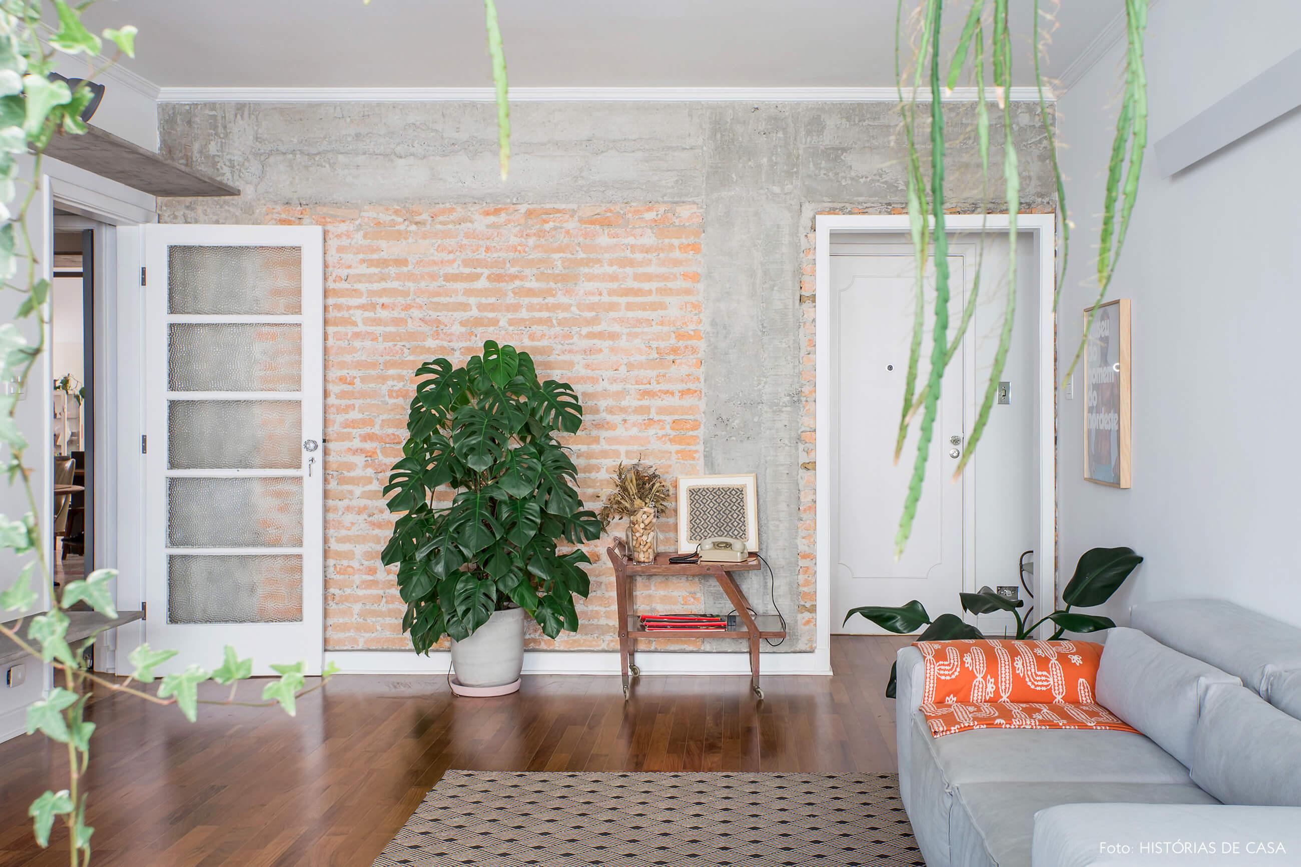 Sala integrada com parede de tijolinho aparente e piso de madeira