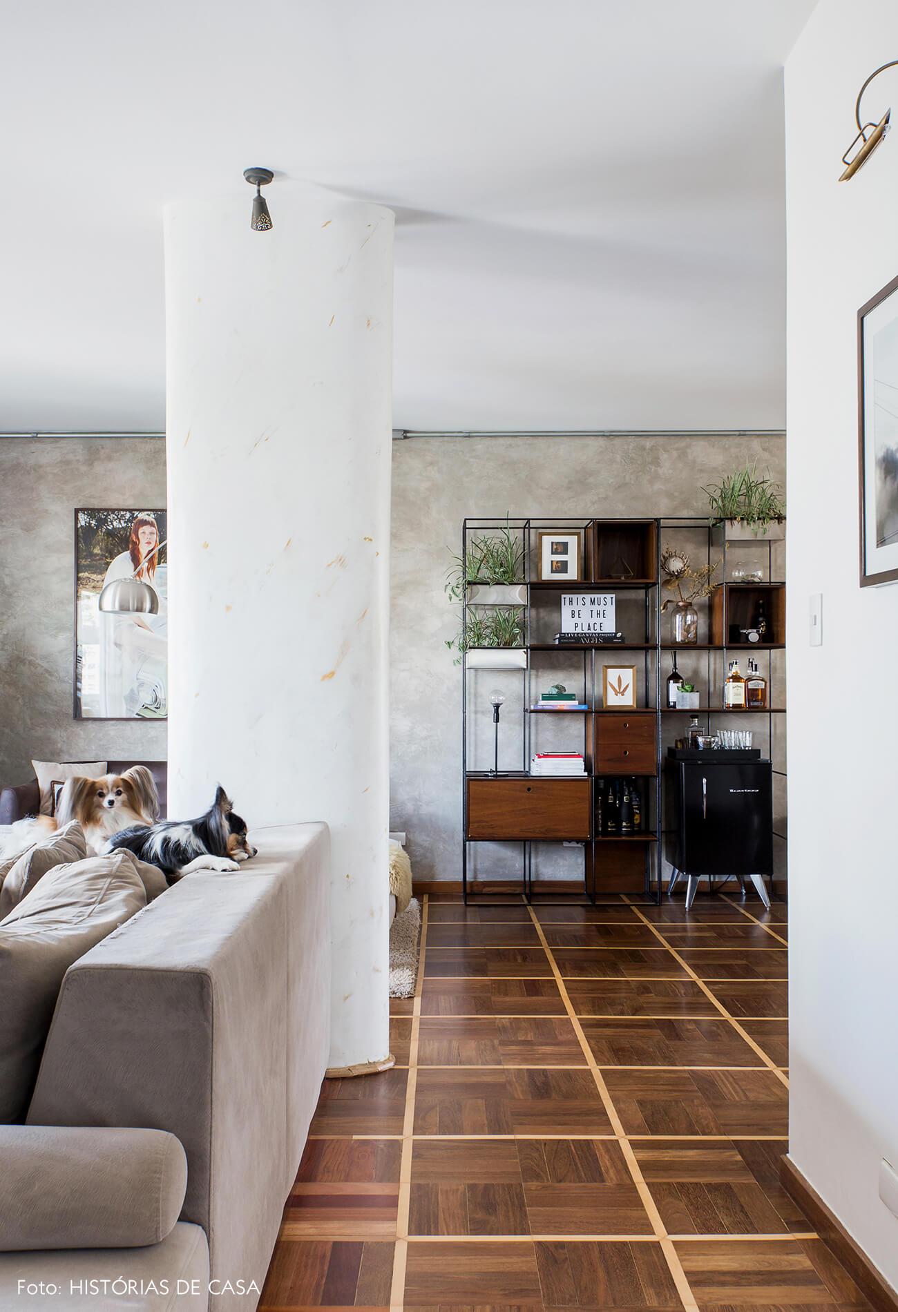 Sala com parede de cimento queimado e piso de parquet