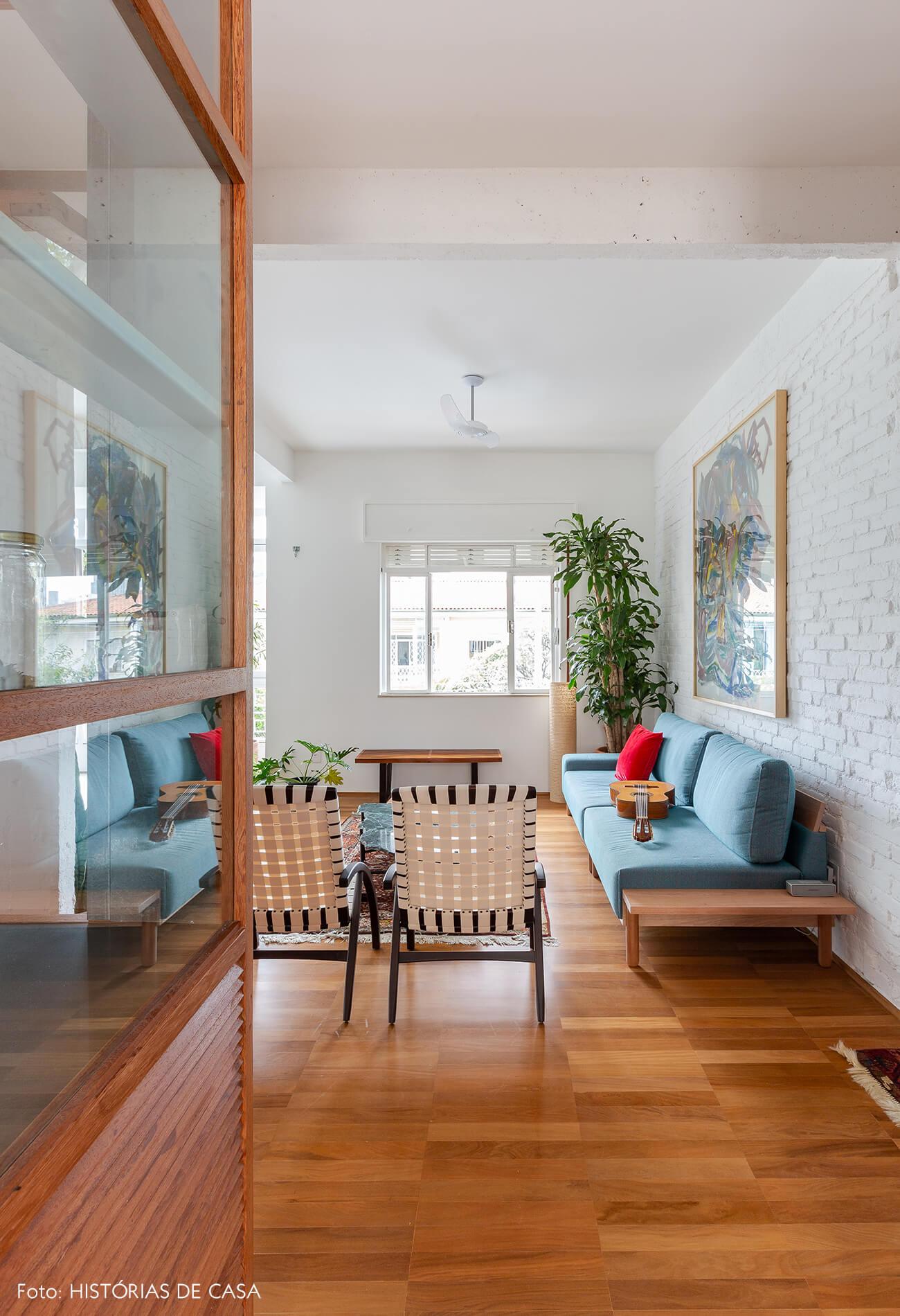 Apartamento reformado com paredes de tijolinho branco e piso de madeira