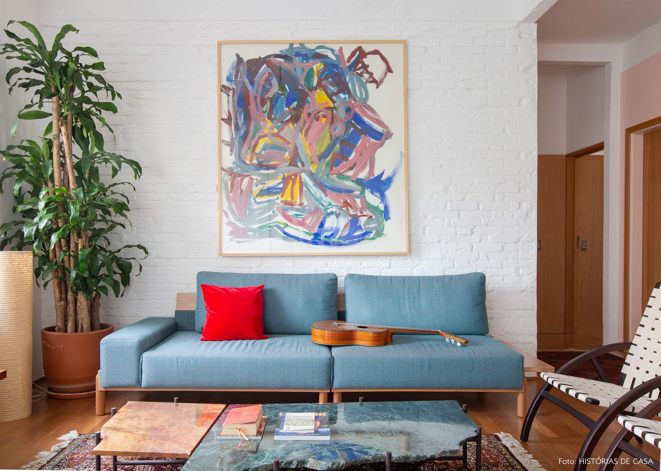 Apartamento reformado com paredes de tijolinho branco e sofá colorido azul