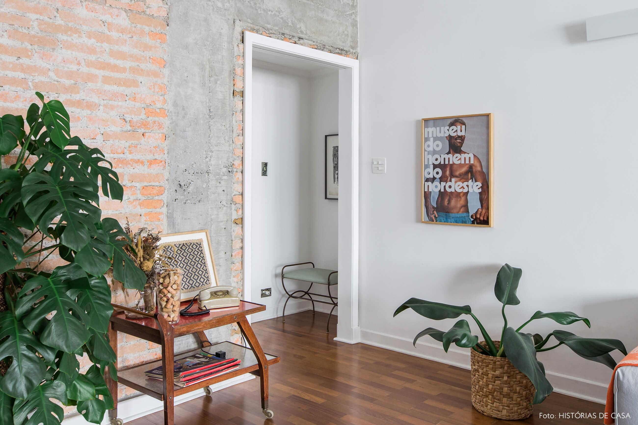 Sala integrada com piso de madeira e parede de tijolinho