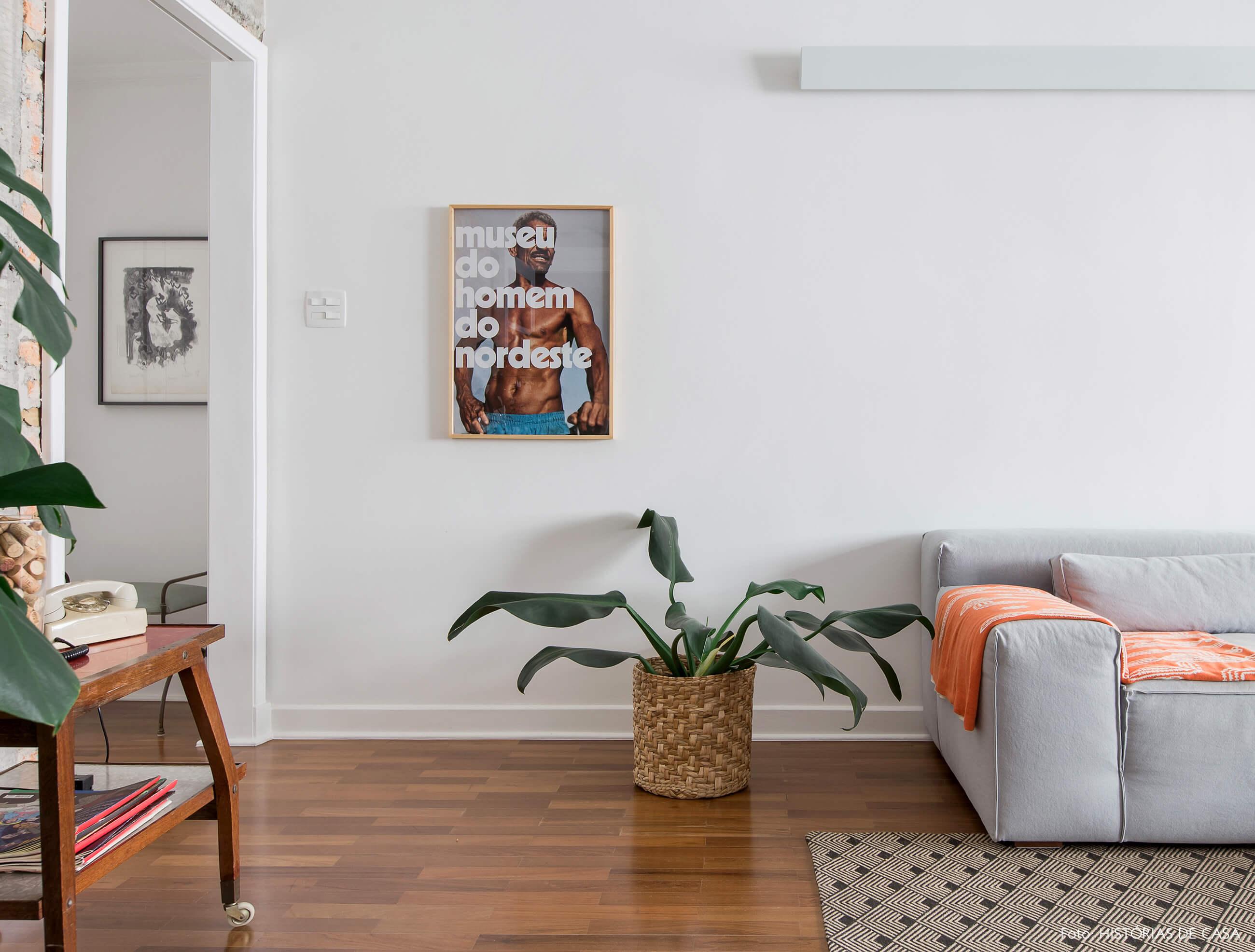 Sala integrada com piso de madeira e sofá cinza