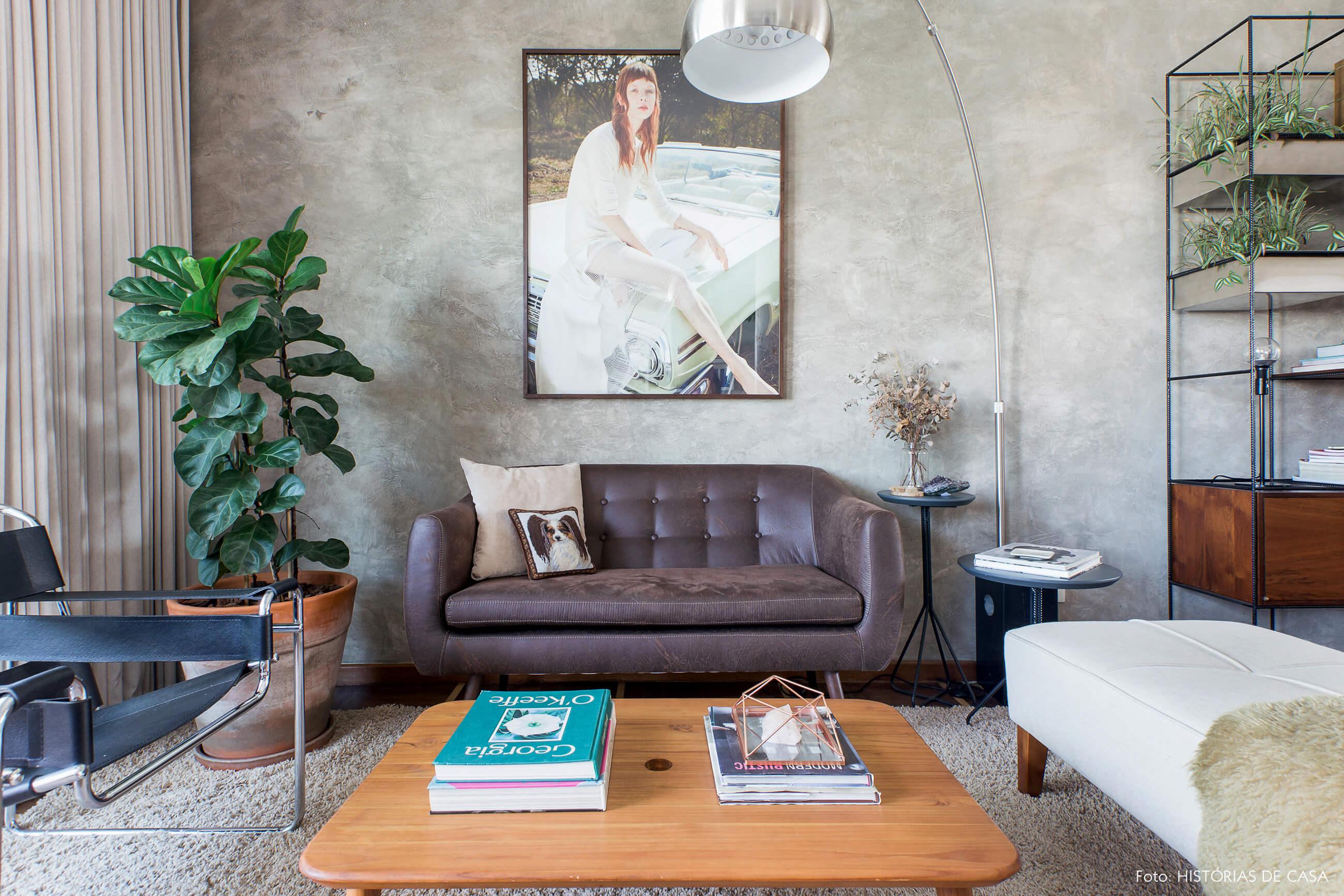 Sala com parede de cimento queimado e sofá de couro
