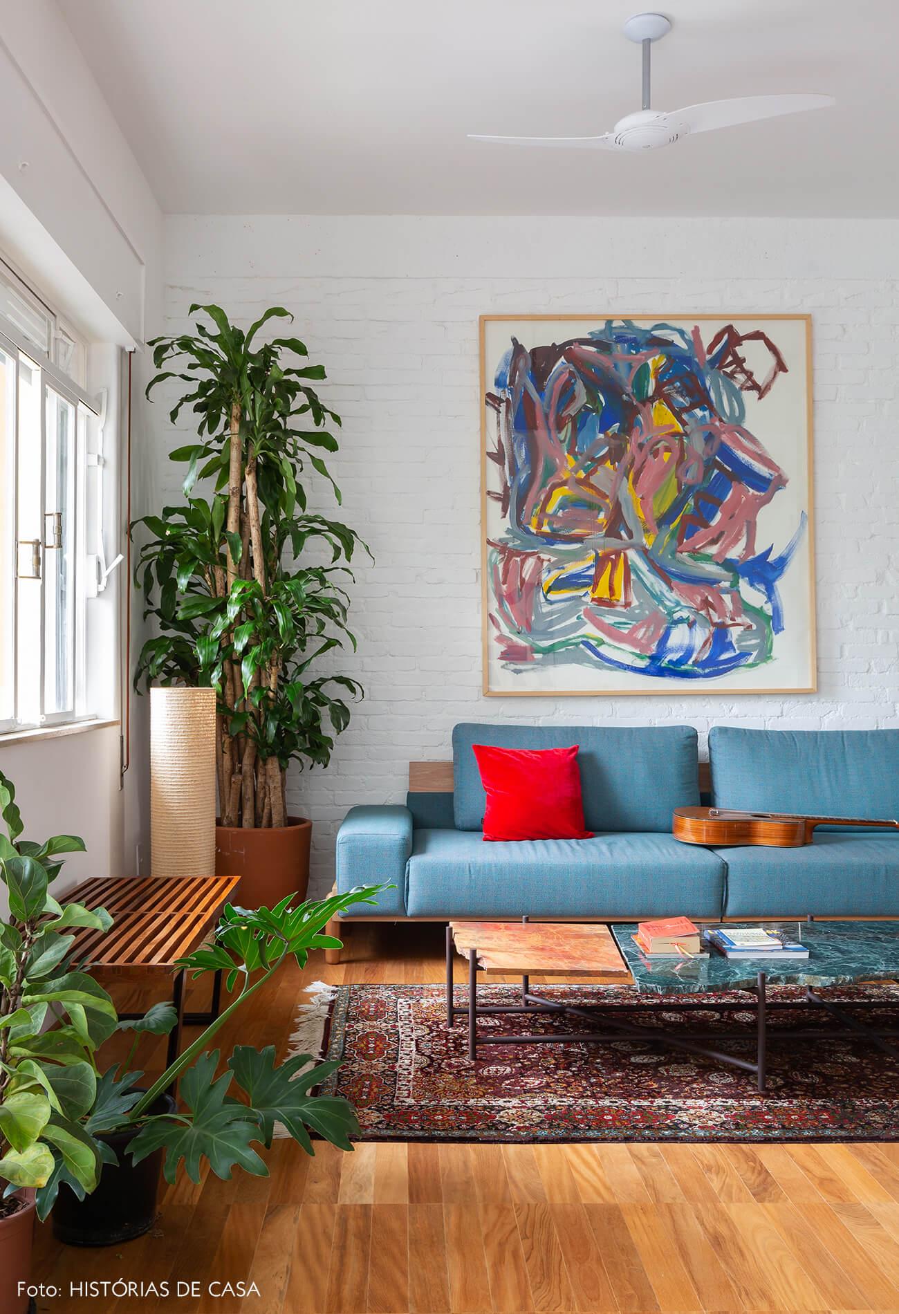 Apartamento reformado com paredes de tijolinho branco e sofá azul