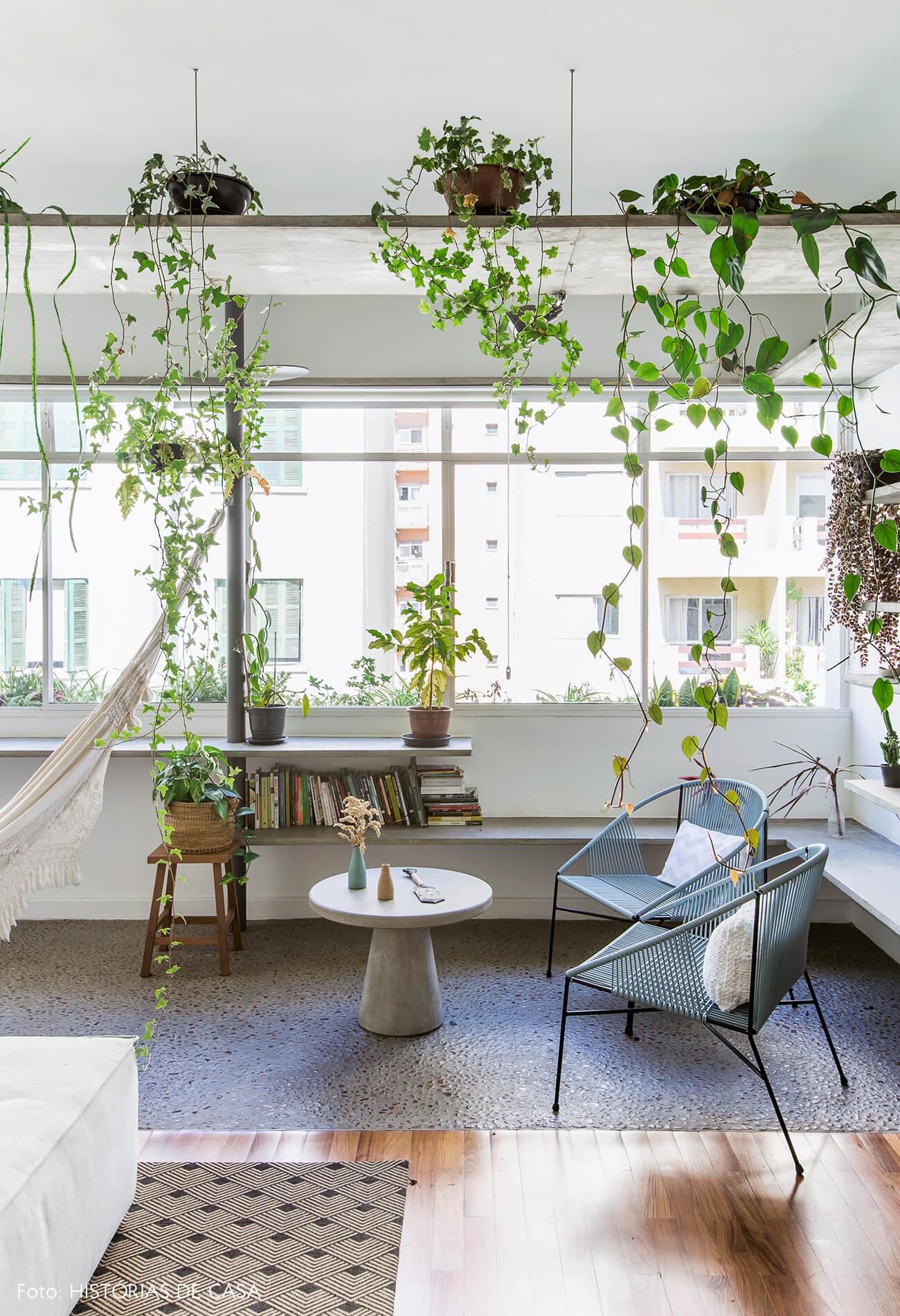 Sala com varanda integrada, piso de seixos e prateleiras de concreto com plantas