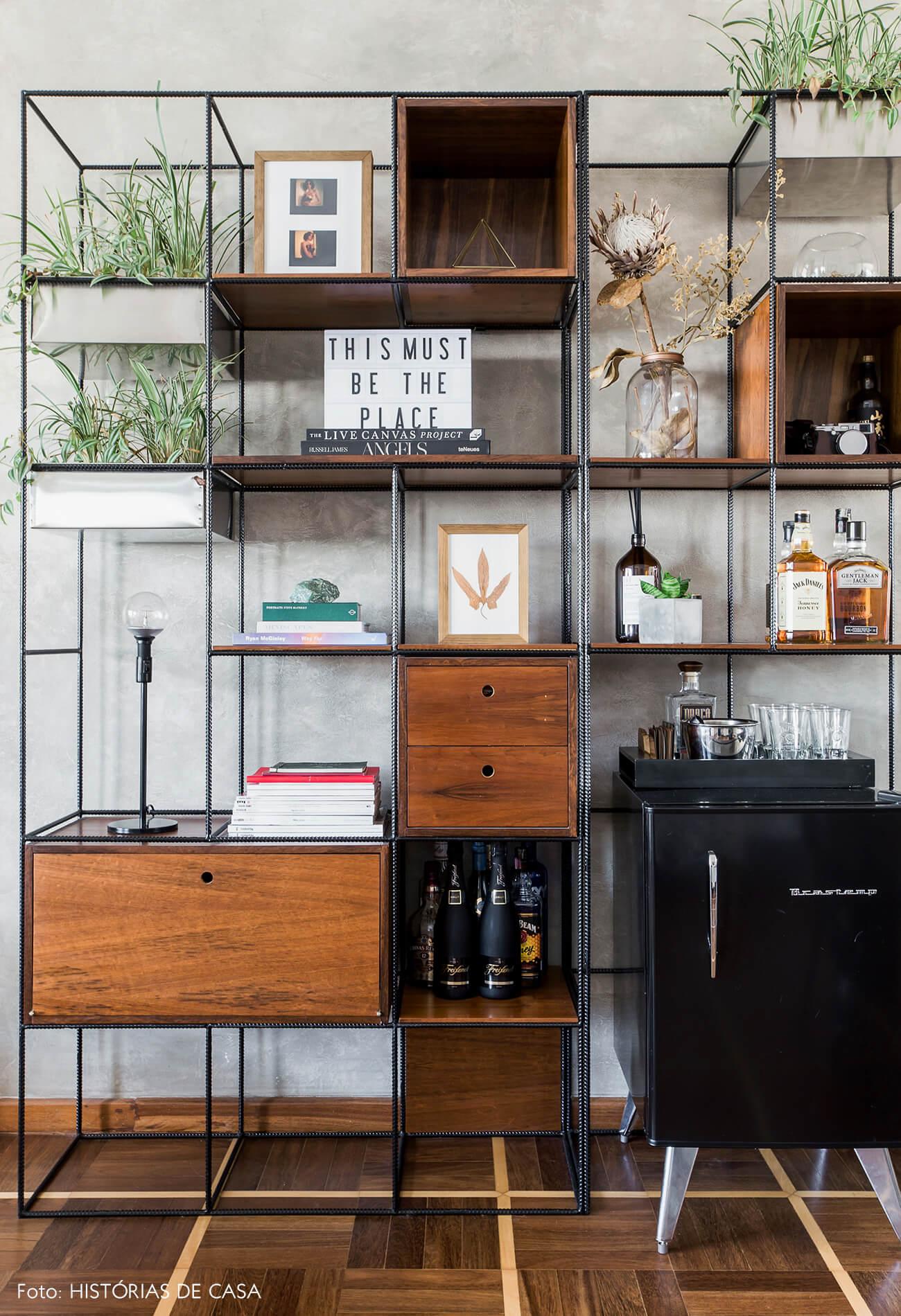 Sala com parede de cimento queimado e estante de vergalhão