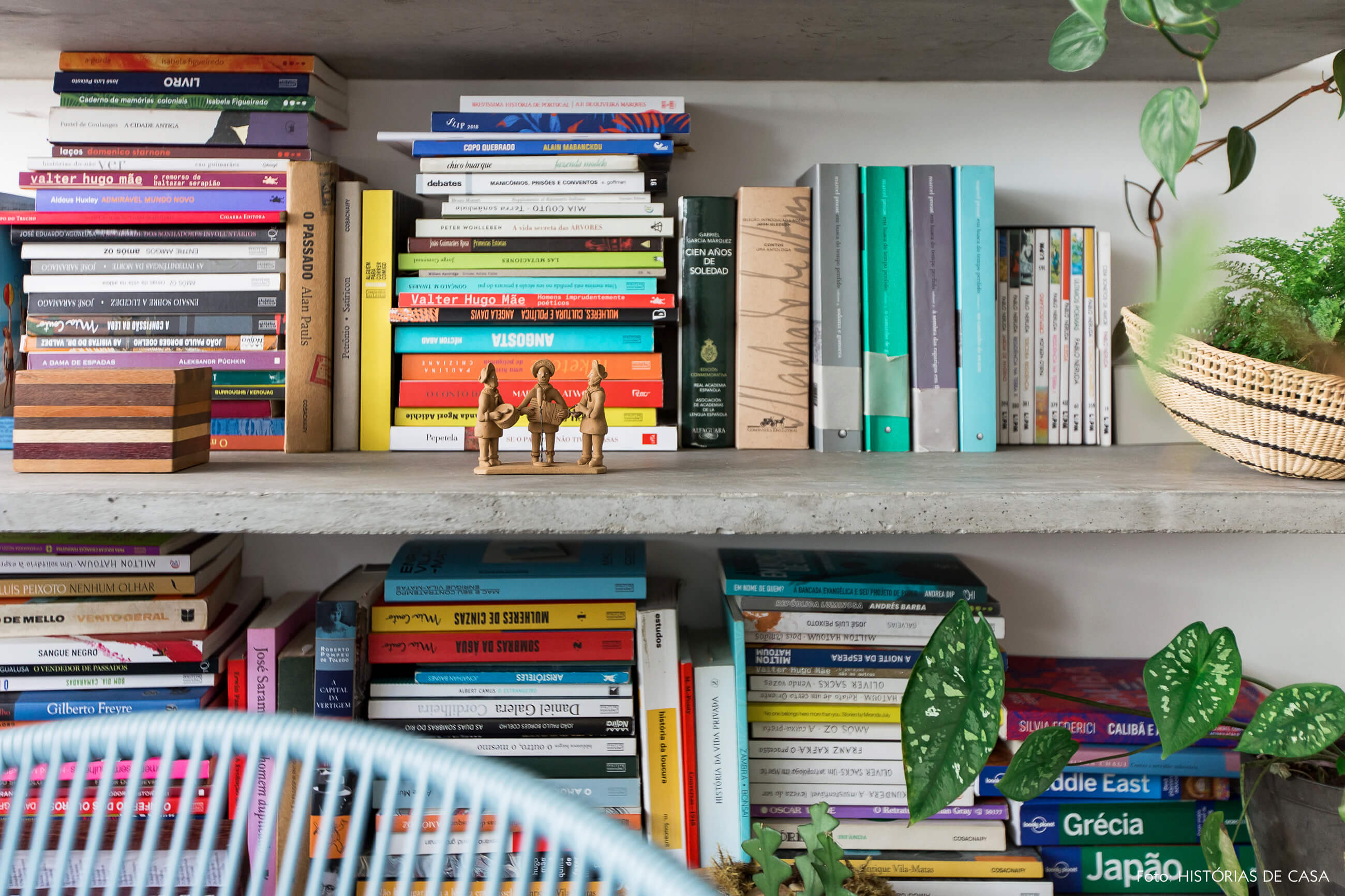 Sala com varanda integrada, piso de seixos e prateleiras de concreto com muitos livros