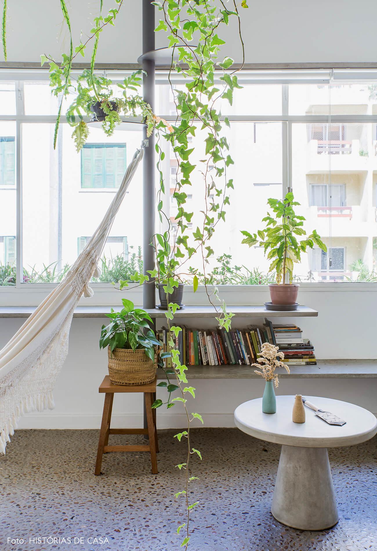 Sala com varanda integrada, prateleiras de concreto com plantas e rede de balanço