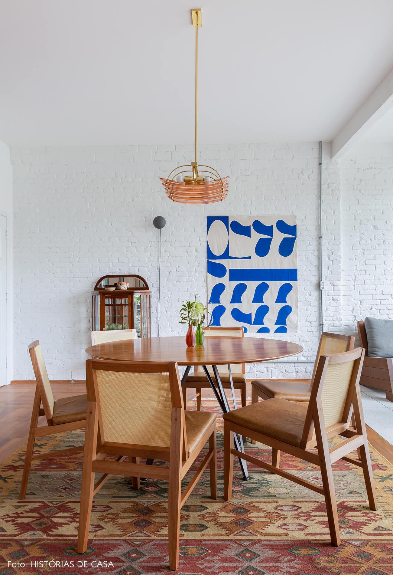 Apartamento reformado com mesa de jantar redonda e parede de tijolinho branco na sala