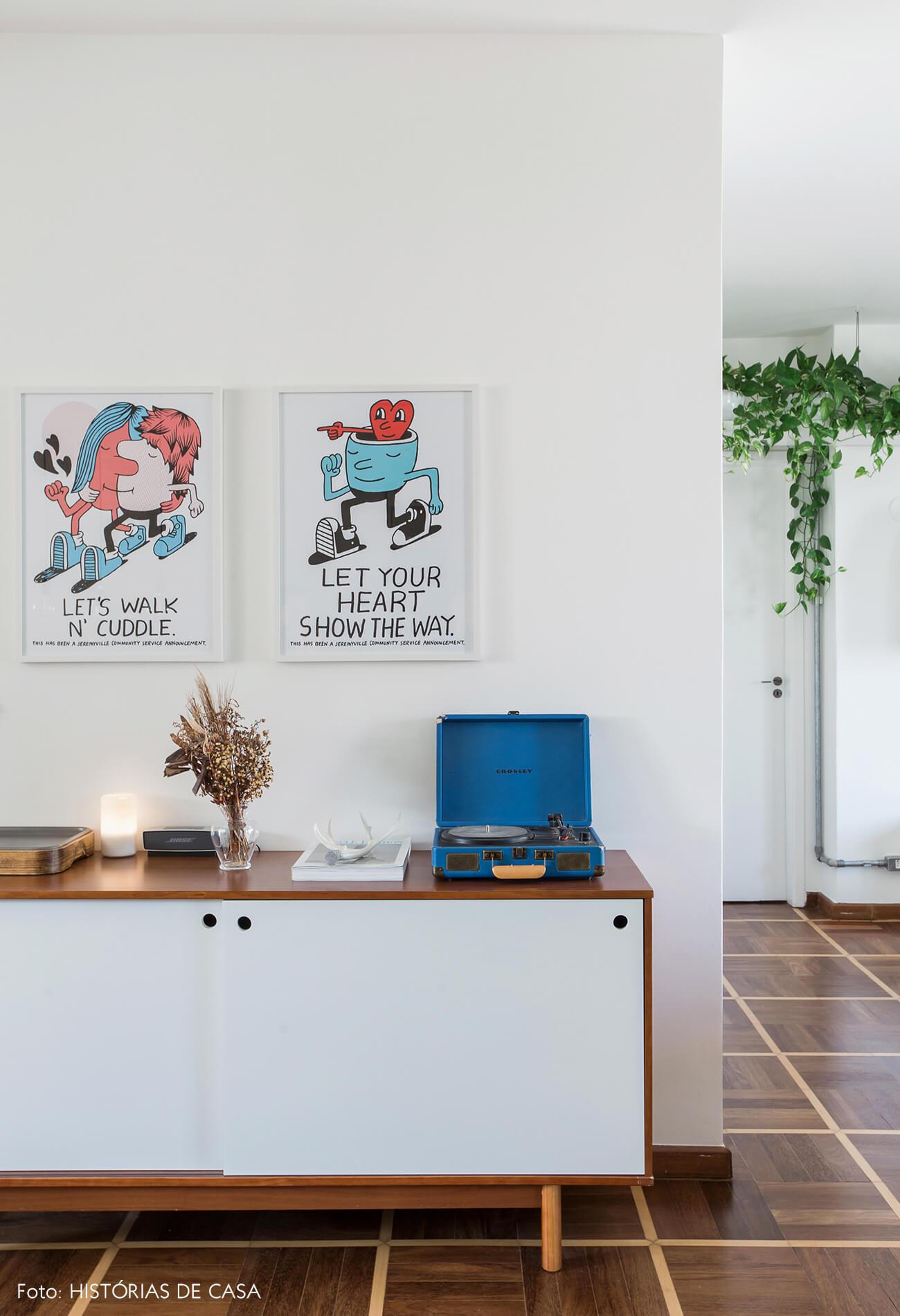 Estante branca na sala com plantas pendentes e piso de parquet