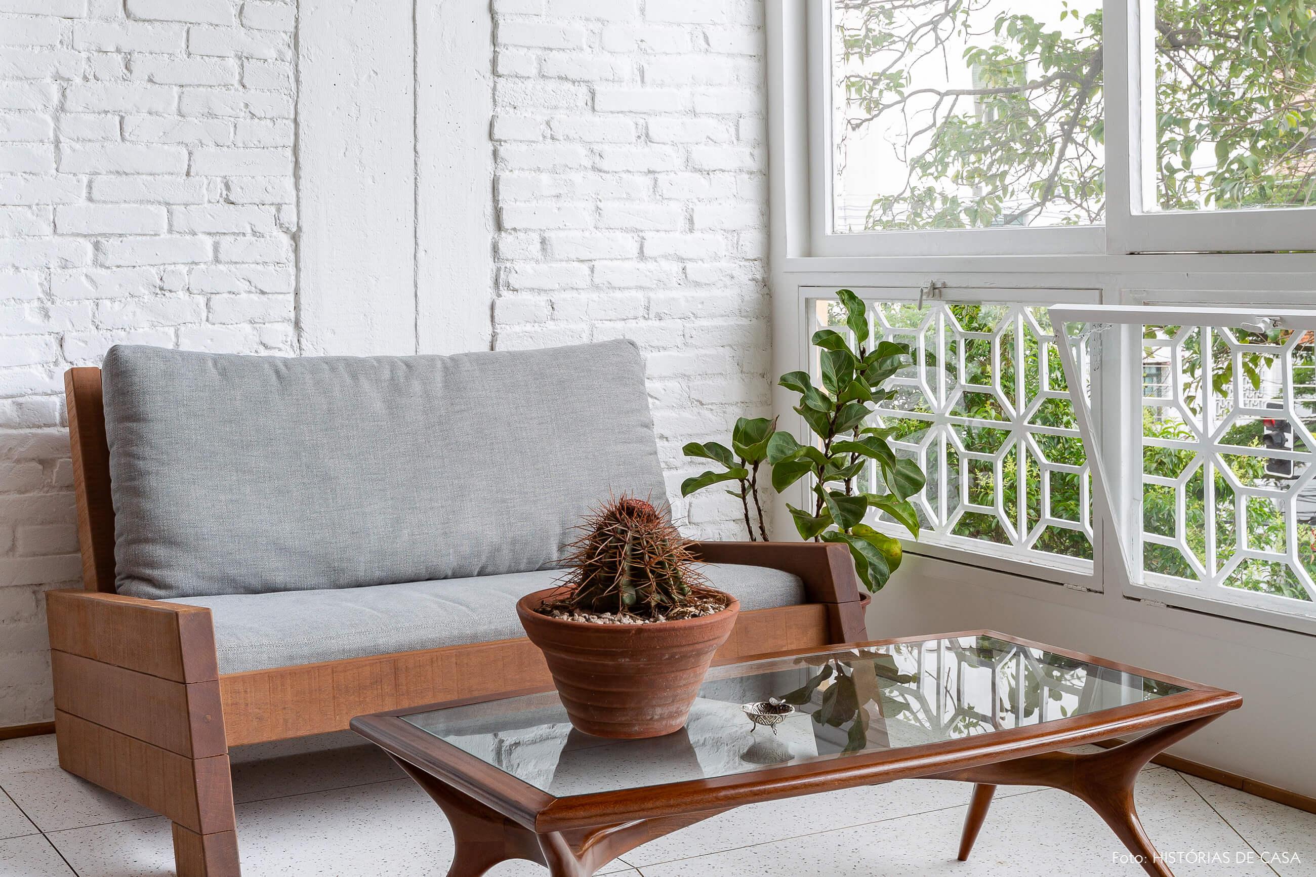 Apartamento com parede de tijolinho branco na sala e móveis antigos de madeira