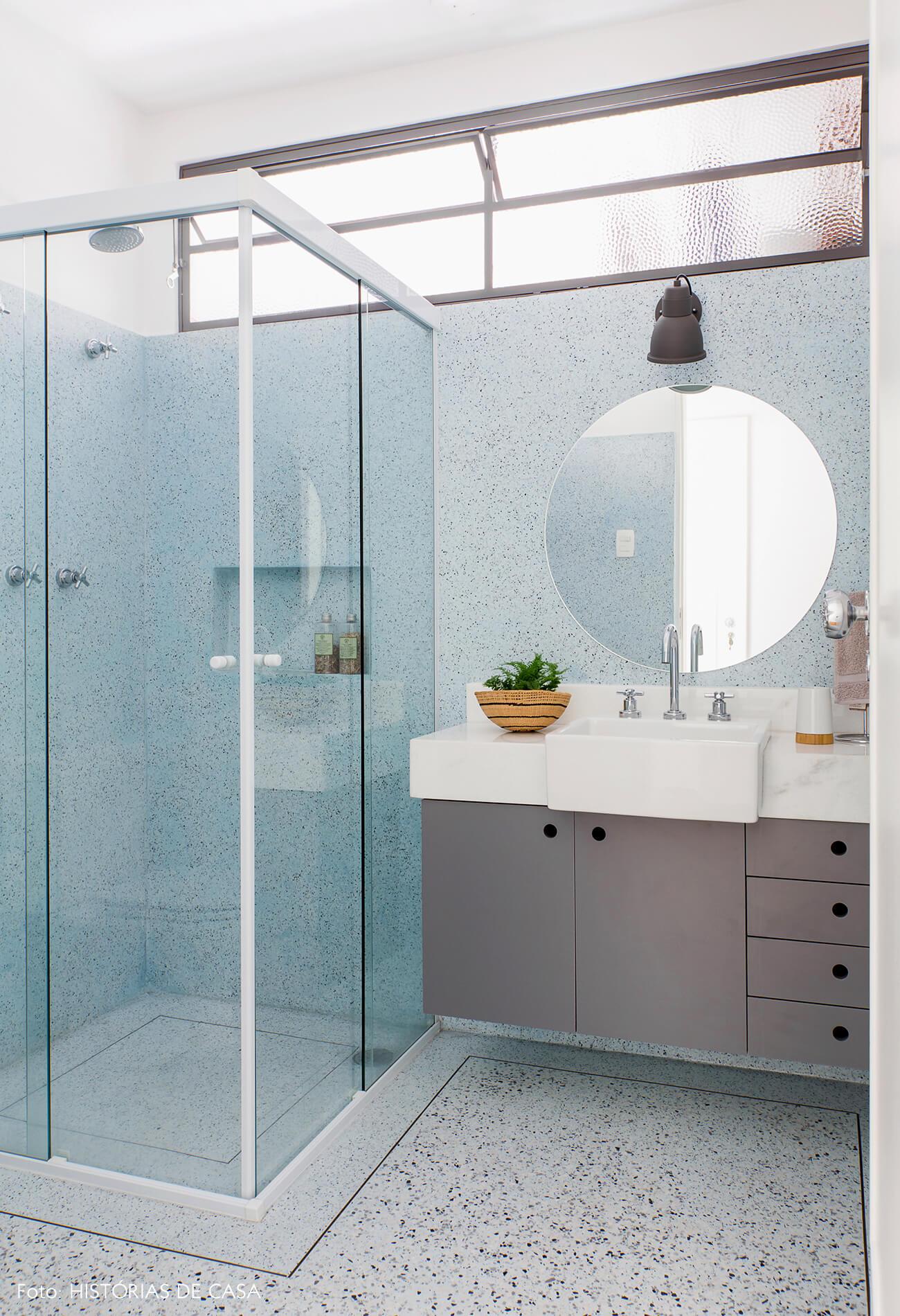 Banheiro de granilite azul no piso e na parede, espelho redondo