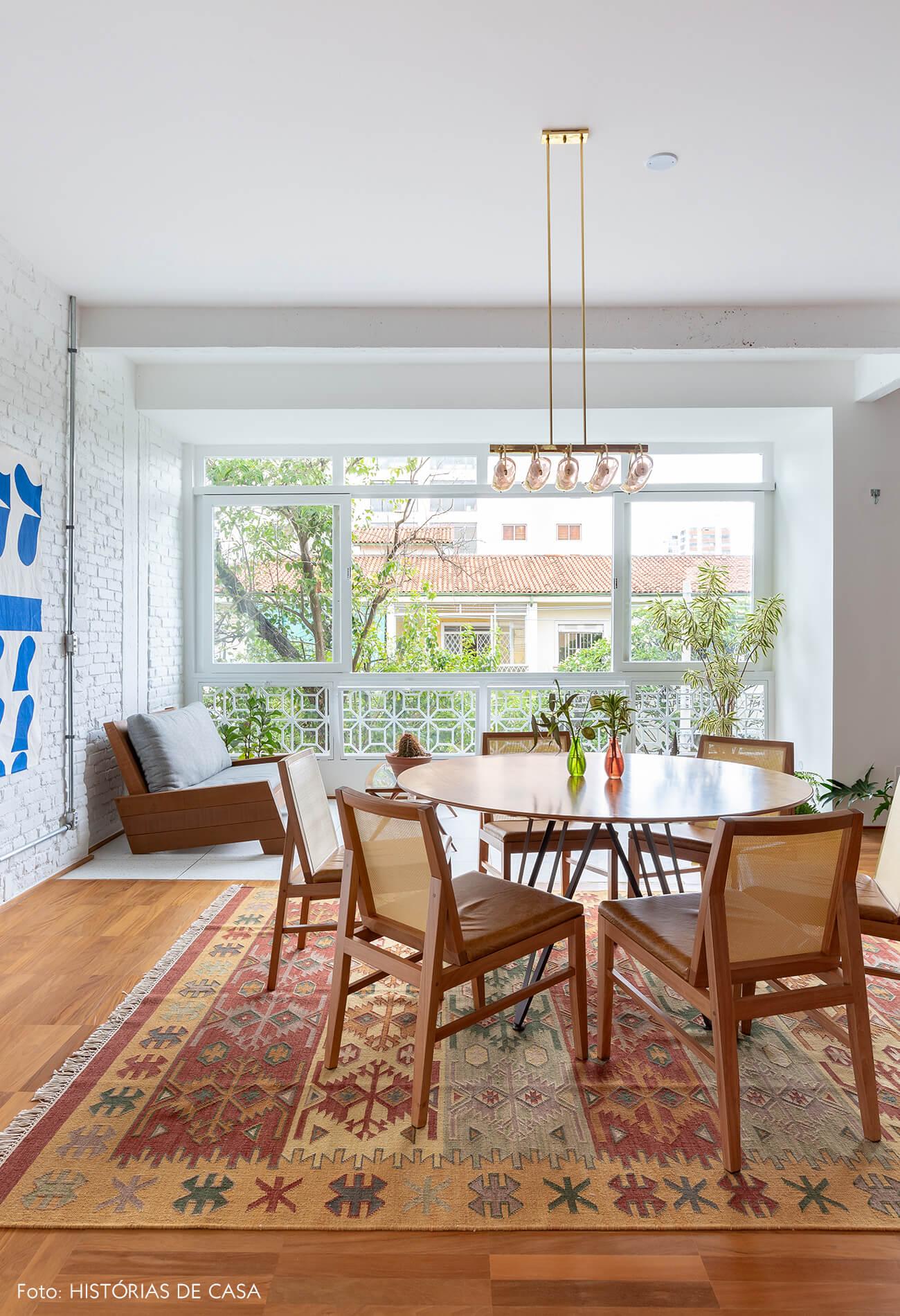Sala de jantar com varanda integrada e mesa redonda de madeira