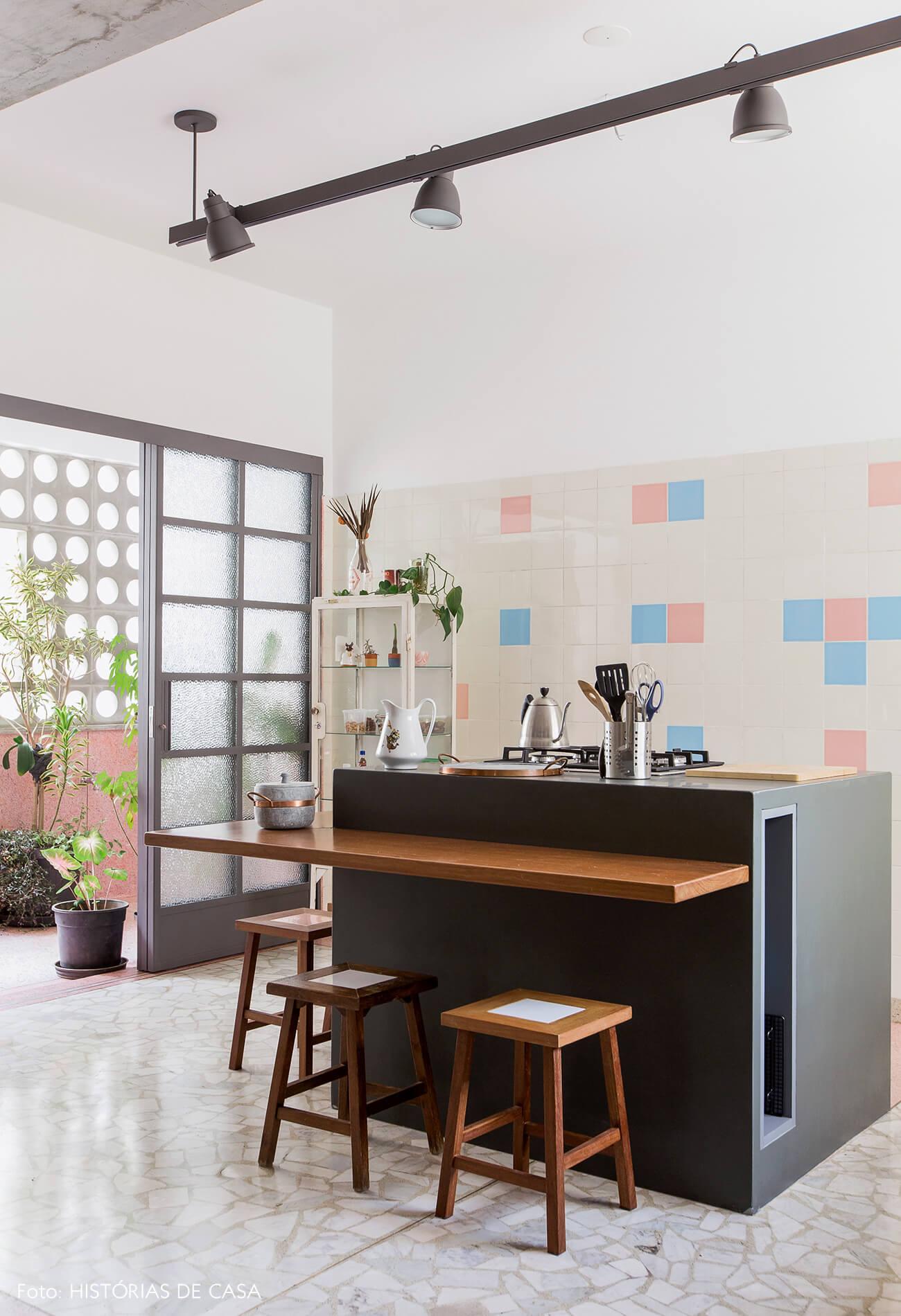 Cozinha vintage reformada com piso de granilite e ilha central com banquetas