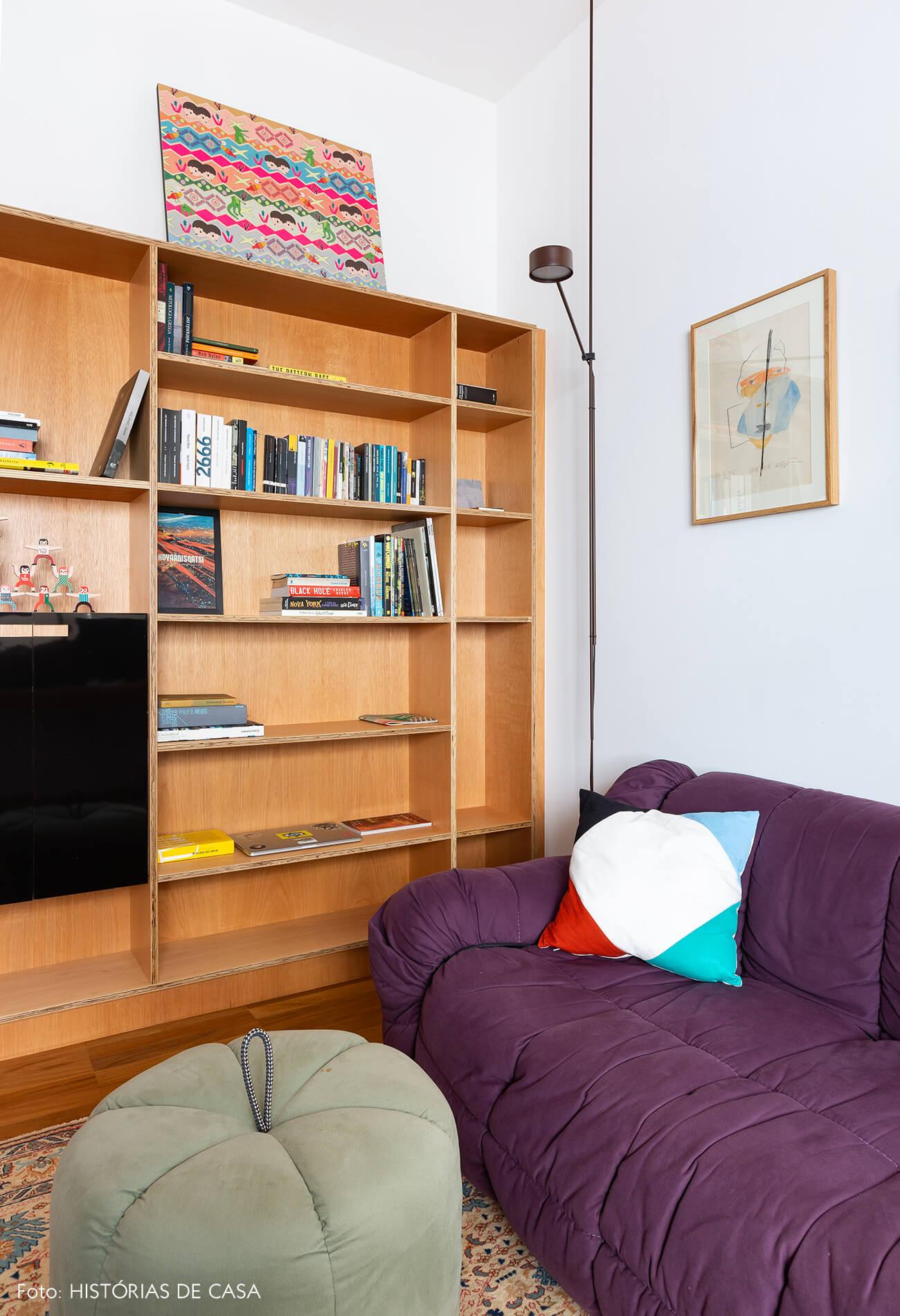 Home office com estante de marcenaria e sofá colorido