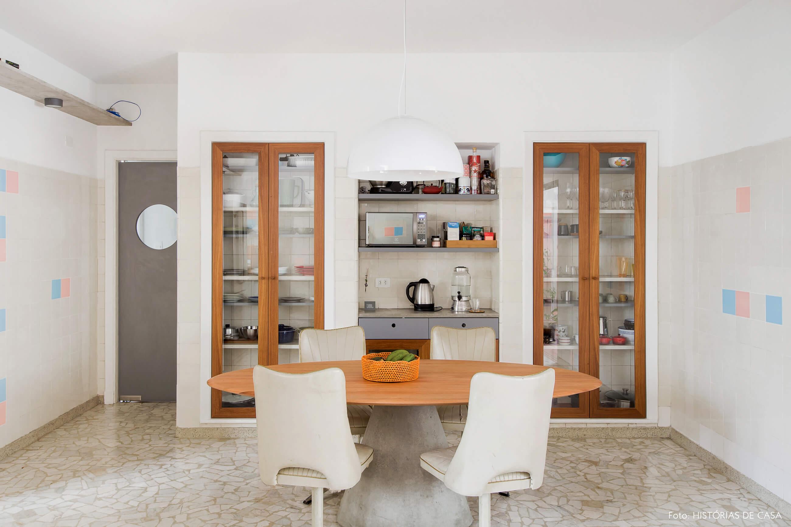 Cozinha vintage reformada com piso de granilite e armários de madeira com portas de vidro