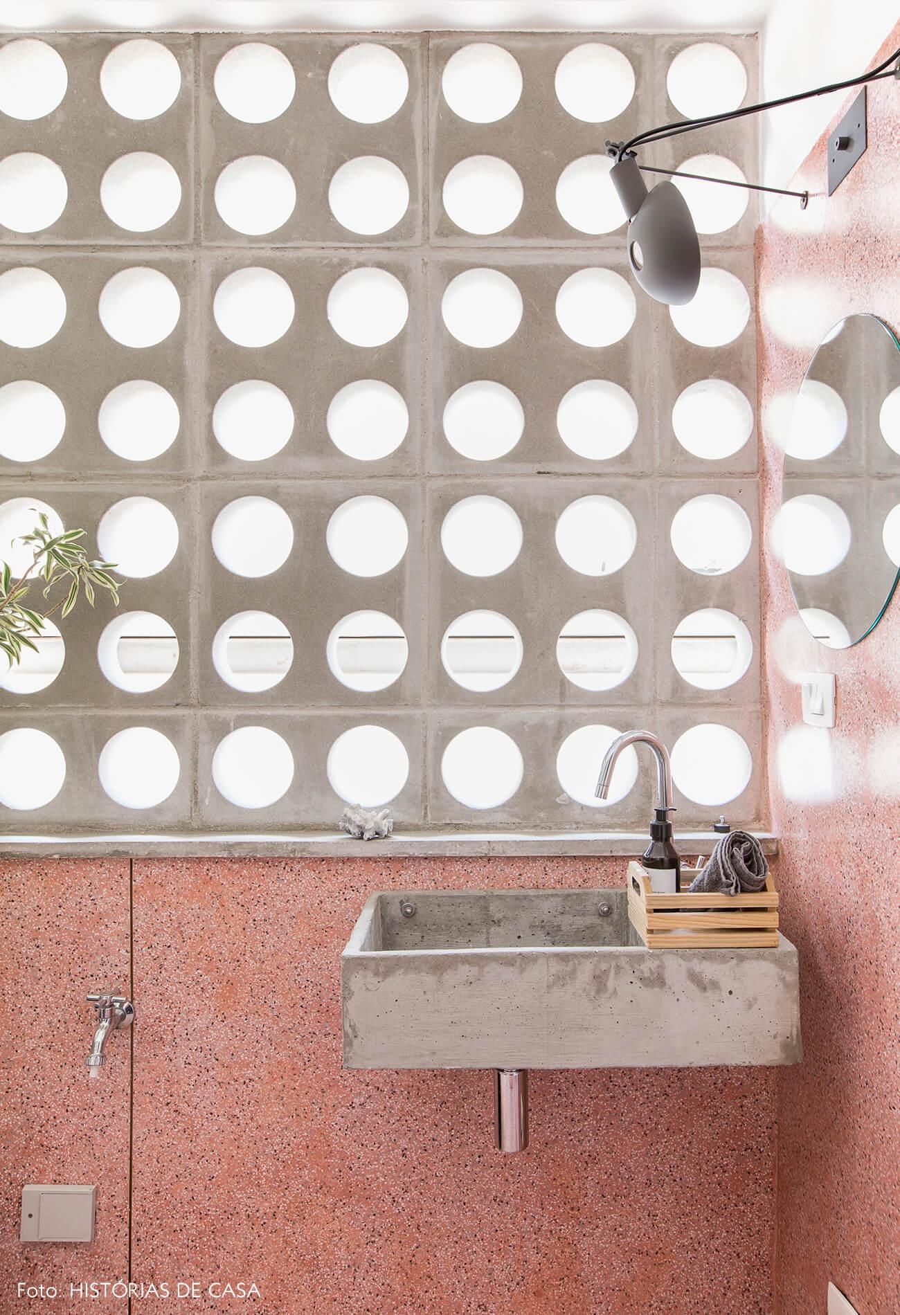 Banheiro com piso e paredes de granilite rosa e fachada de cobogós