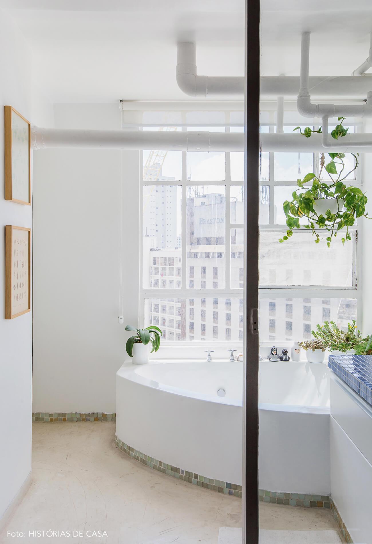 Banheiro com parede de vidro e muitas plantas