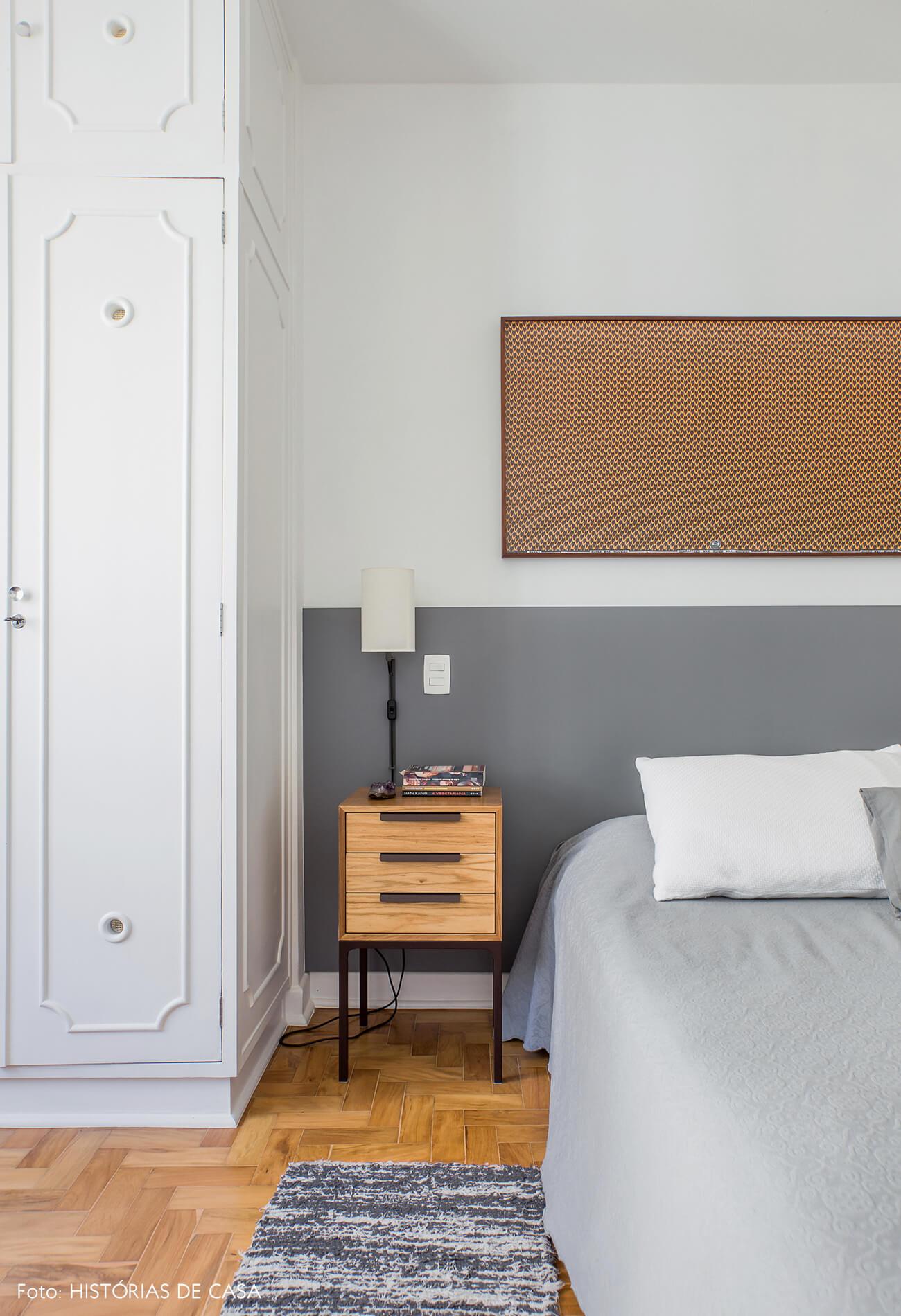 Quarto com meia parede pintada de cinza na cabeceira