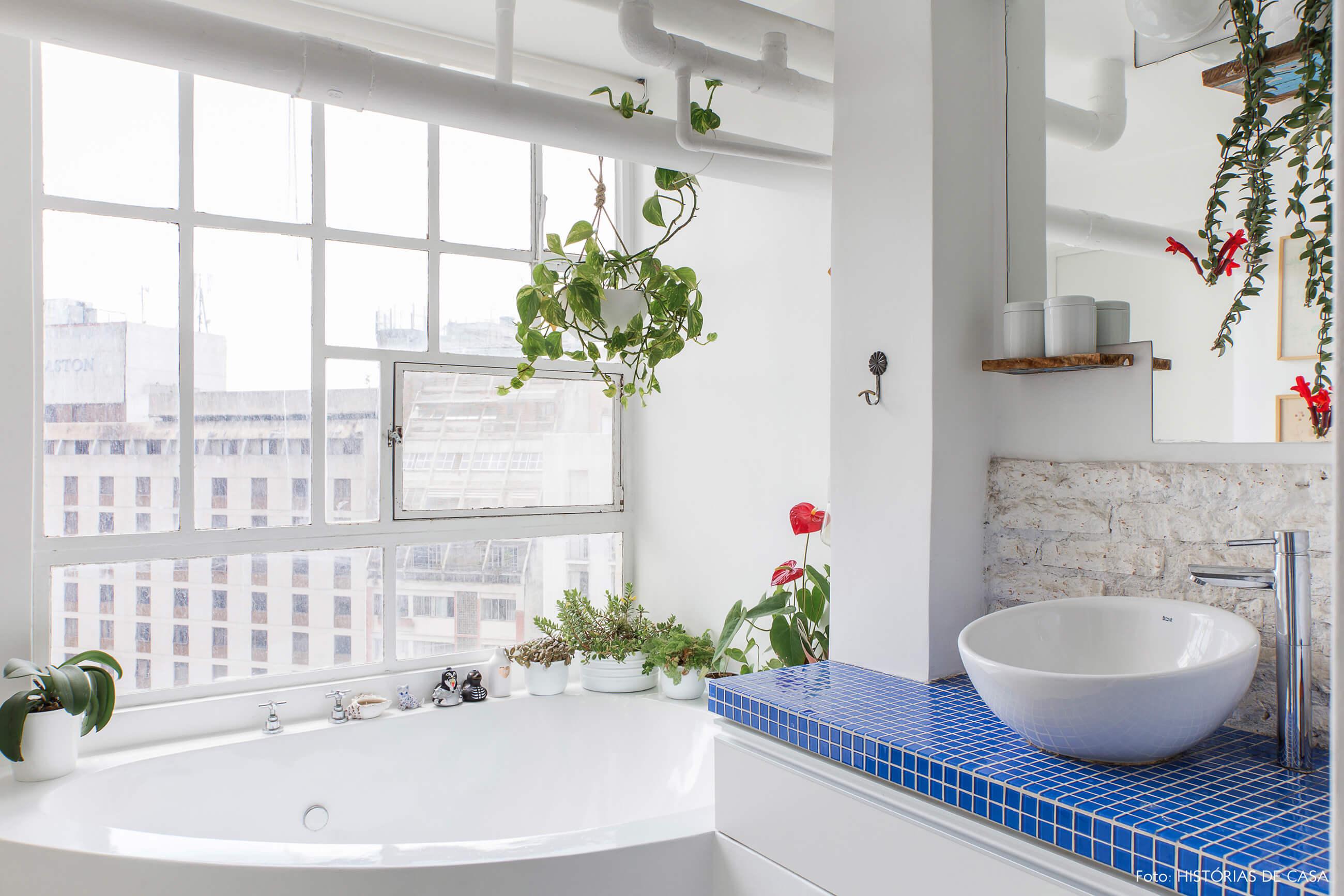Banheiro com parede de vidro e banheira
